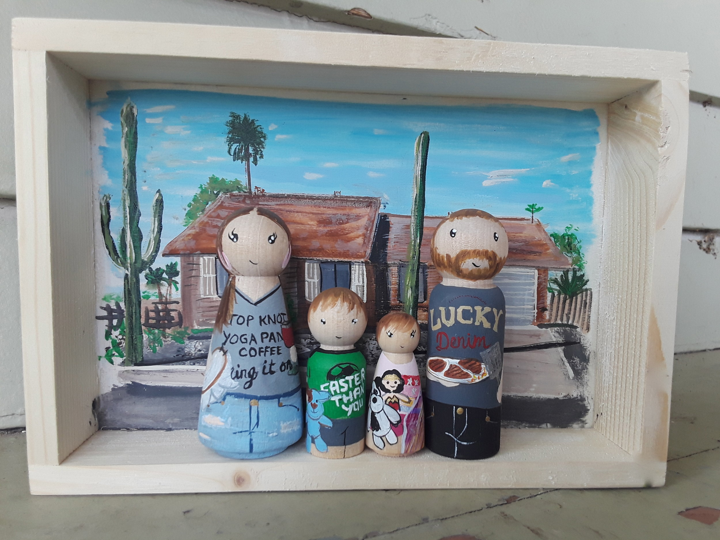 Family home - This Shadow Box and Peg Doll family is bursting with details. As a back drop is their beautiful home in Arizona, featuring their amazing cacti which I loved painting. Each little peg dolls is holding something typical for them. The mother is an amazing cross stitch artist and is holding her embroidery hoop in the one hand and a glass of red wine in the other! Her husband is holding a plate of steaks (red wine AND steaks??? The perfect combination! :)) and the kids are each dressed in their favorite outfits and holding their most loved stuffy toys.Box Size 6x8 inches. 4 peg dolls. Starts at $110