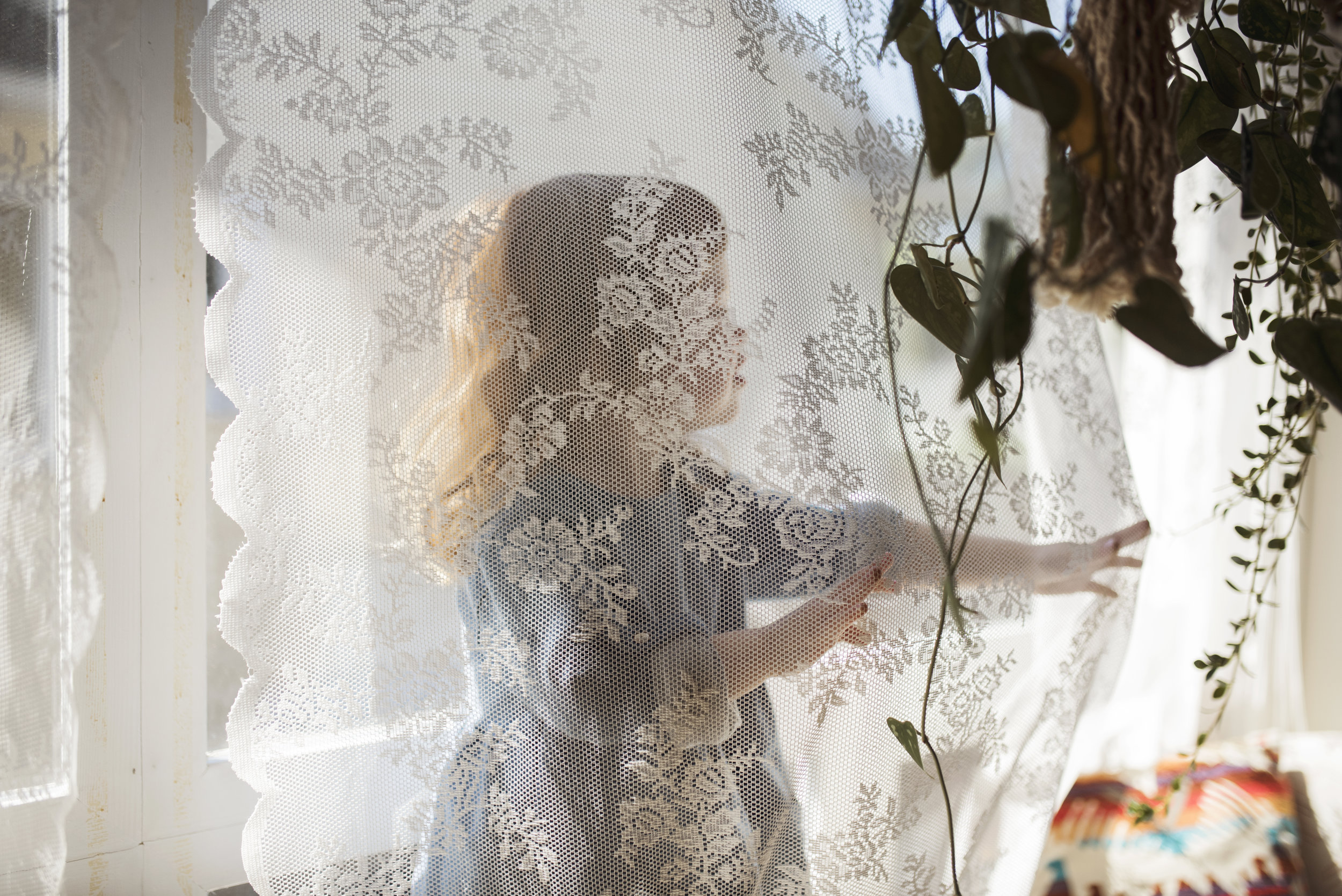 Seattle family photographer girl is hiding behind curtain