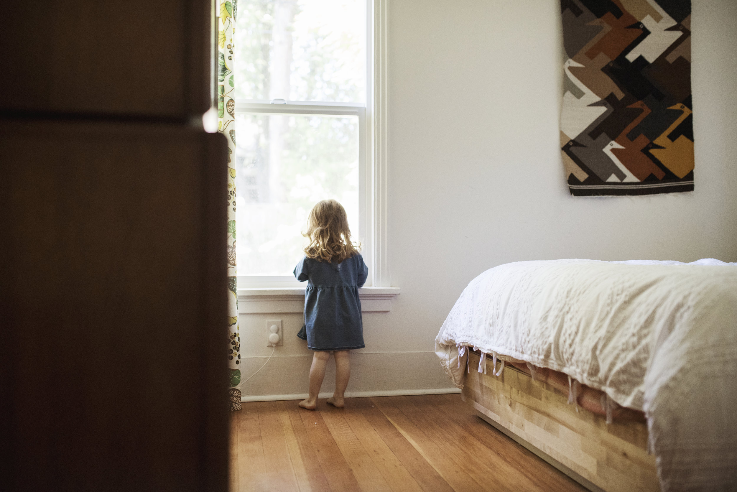 Seattle family photographer girl stands by window
