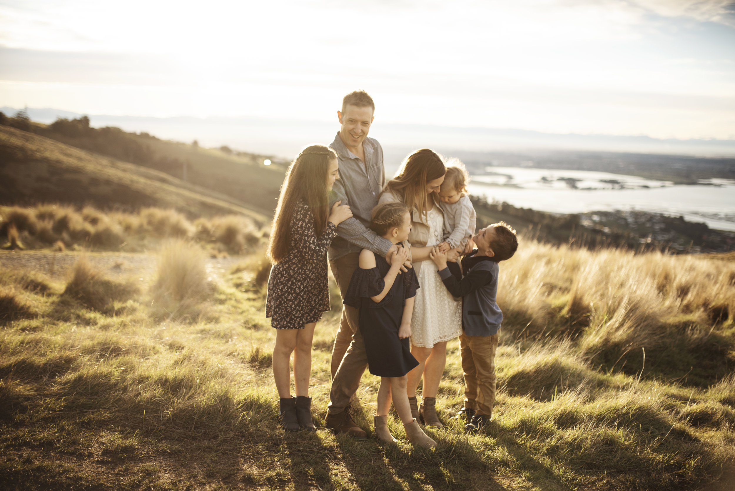 Seattle Family Photographer mom dad and four kids cuddle on a hill