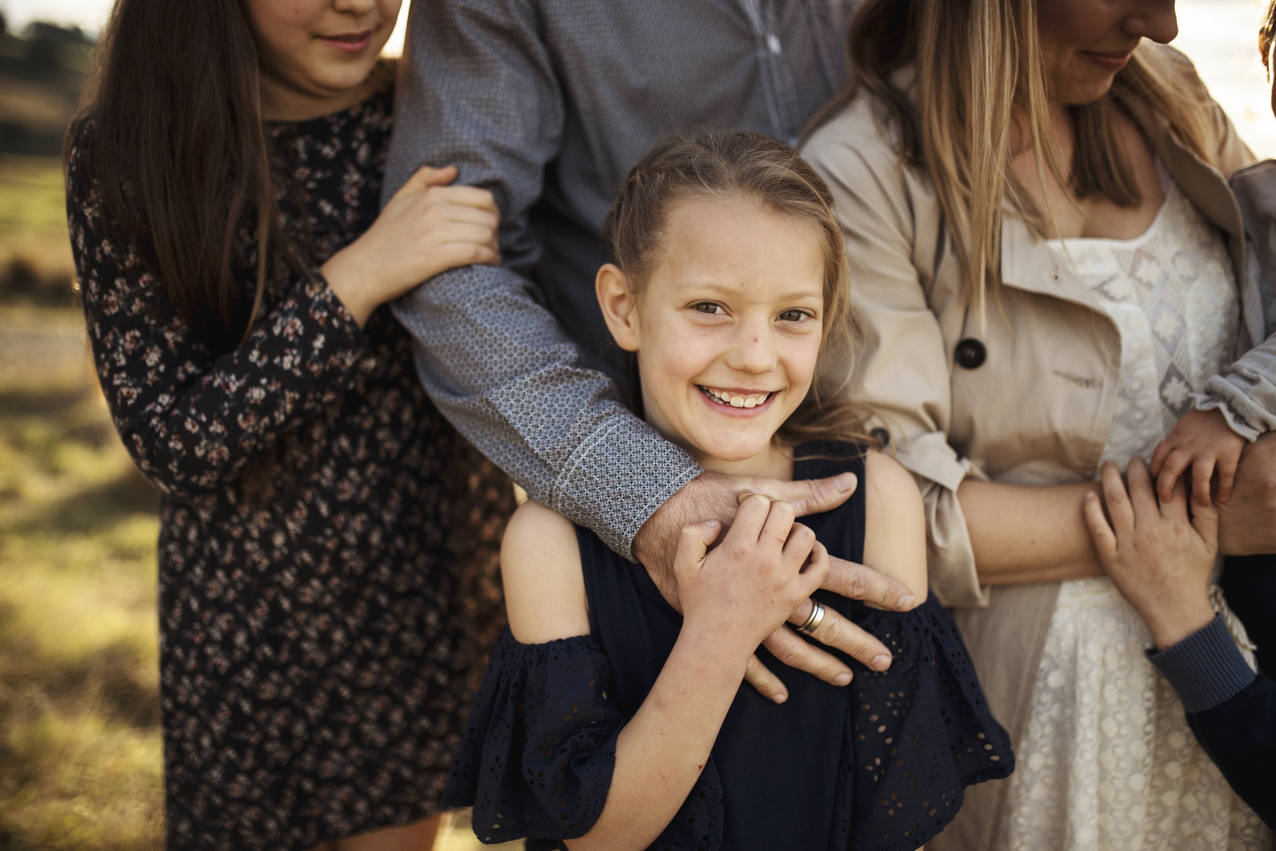 Seattle Family Photographer girl being cuddled by other family members