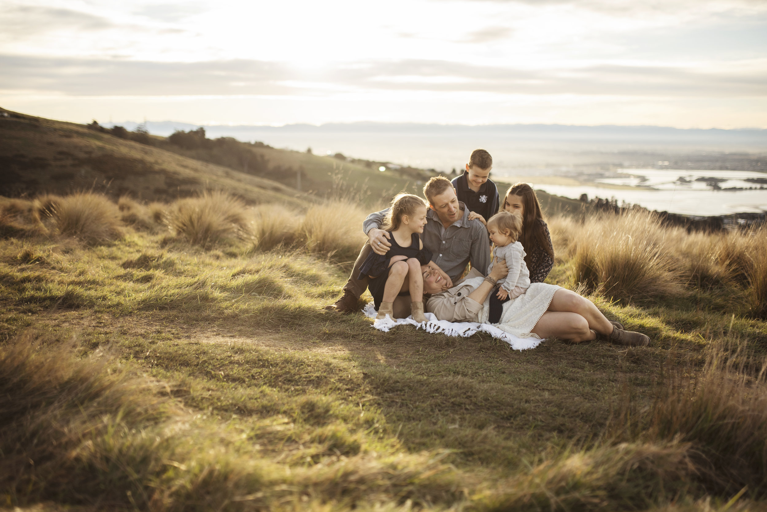 Seattle family photographer mom dad and kids cuddle on a hill