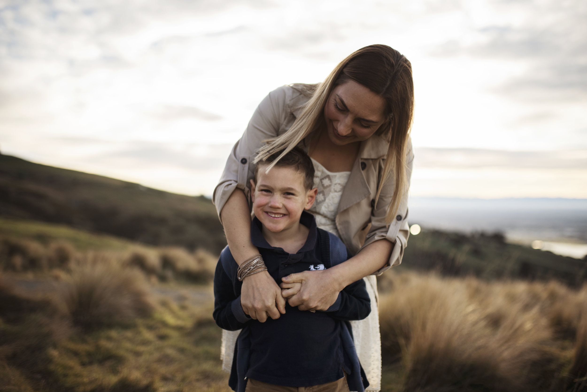 Seattle family photographer mom cuddles with son on a hill