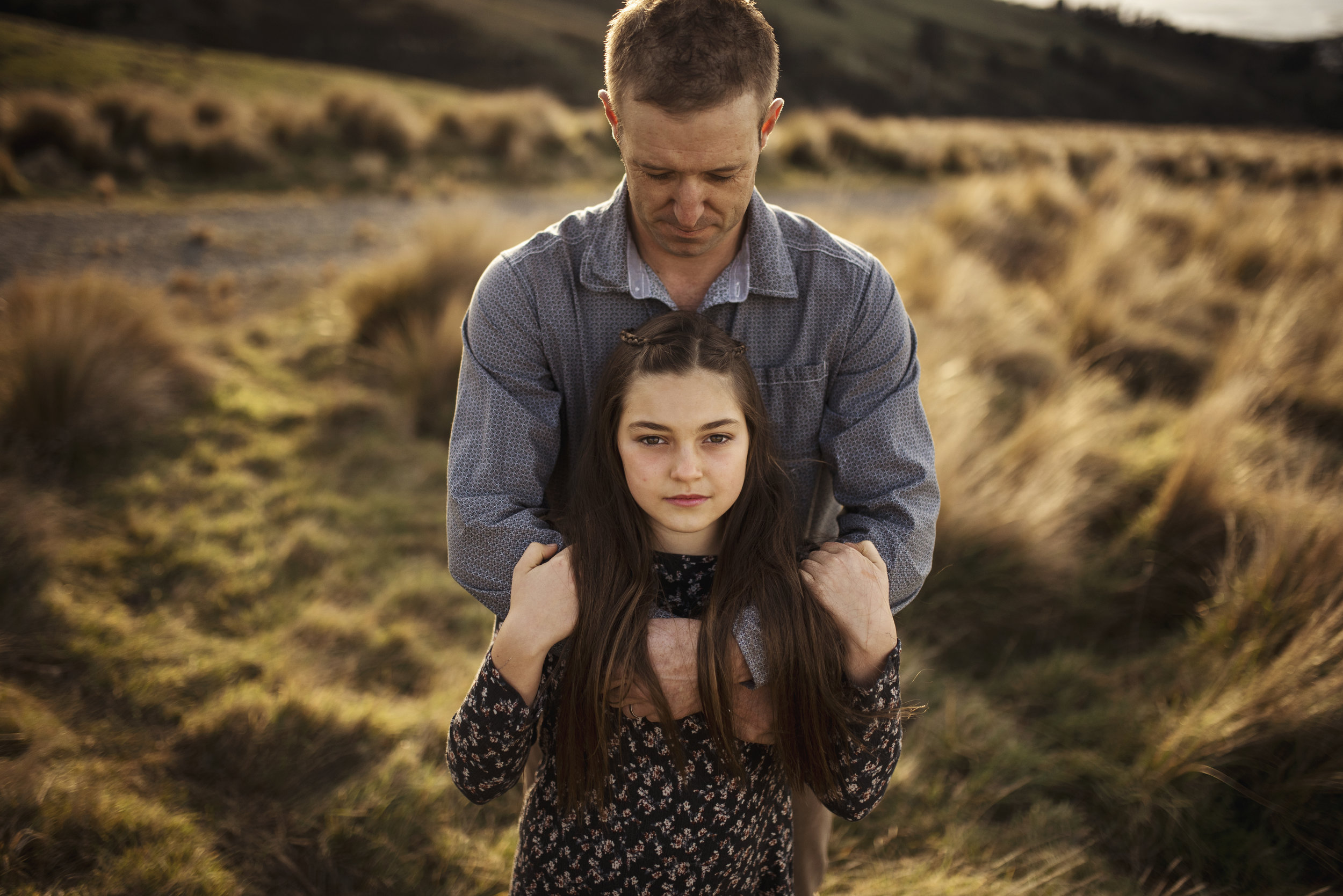 :Lifestyle family photography dad embraces daughter on a hill