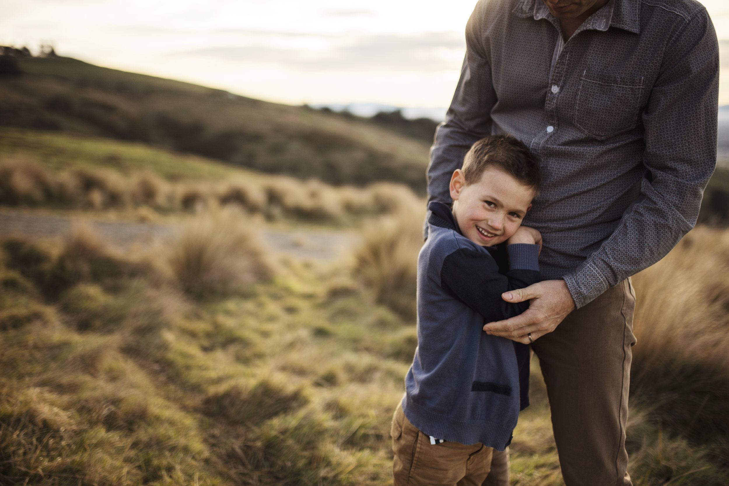 Seattle family photographer dad embraces son on a hill