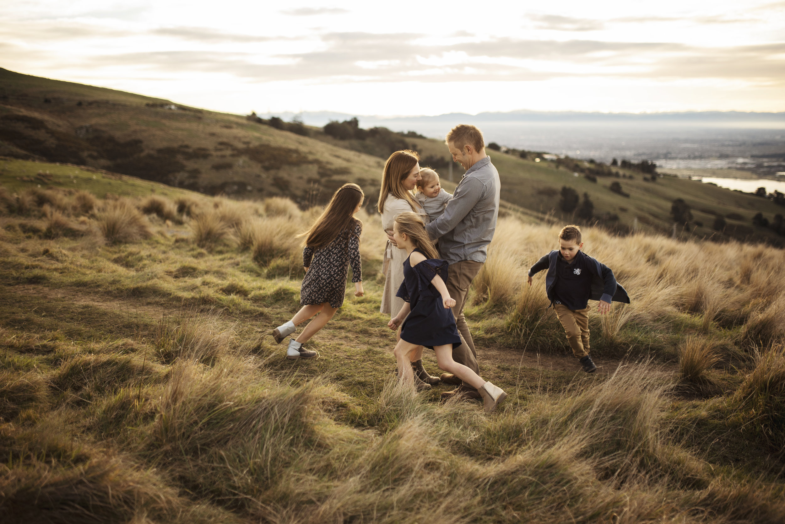 Seattle family photographer kids run around parents on a hill