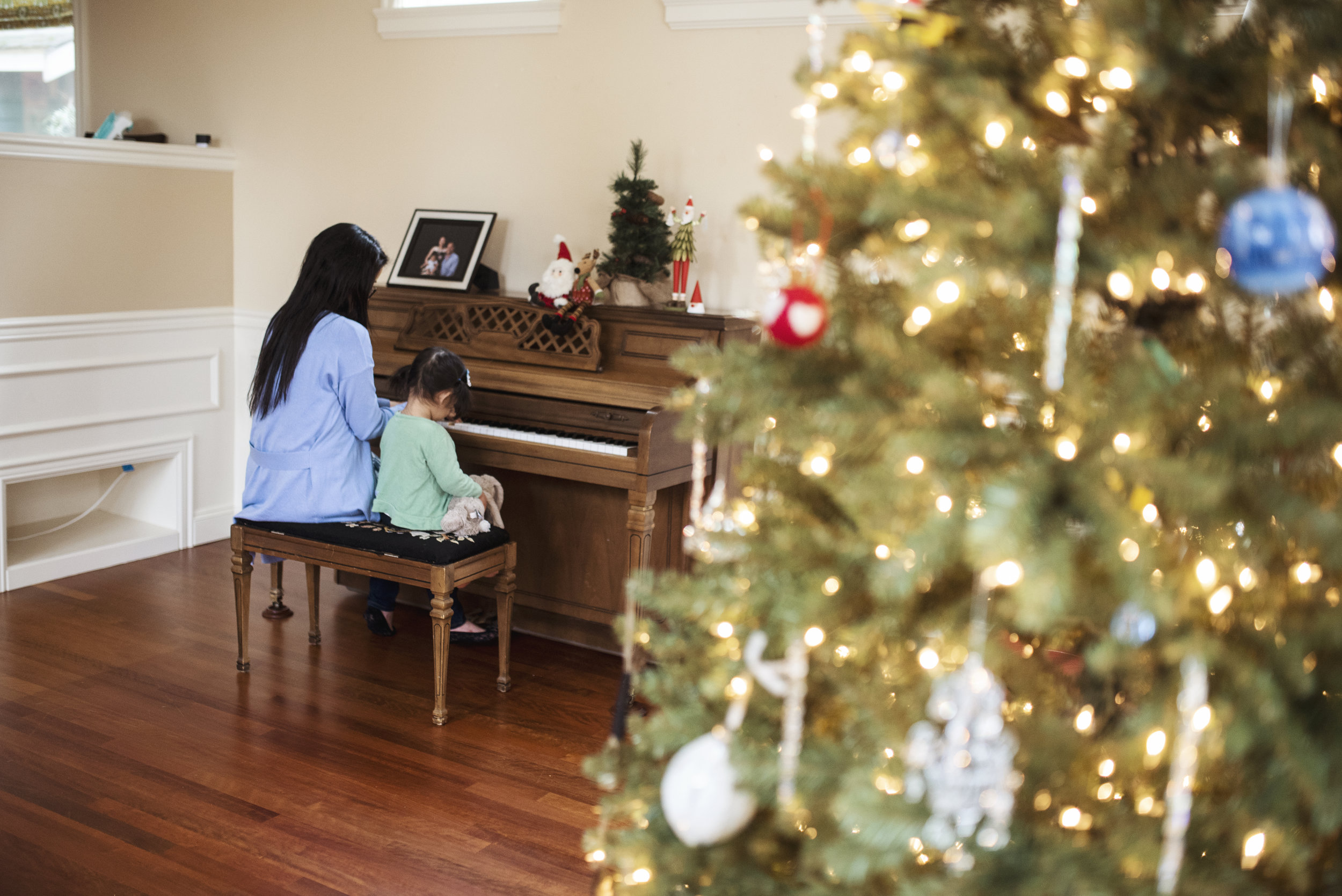 Everett family photographer mom and daughter play piano by Christmas tree