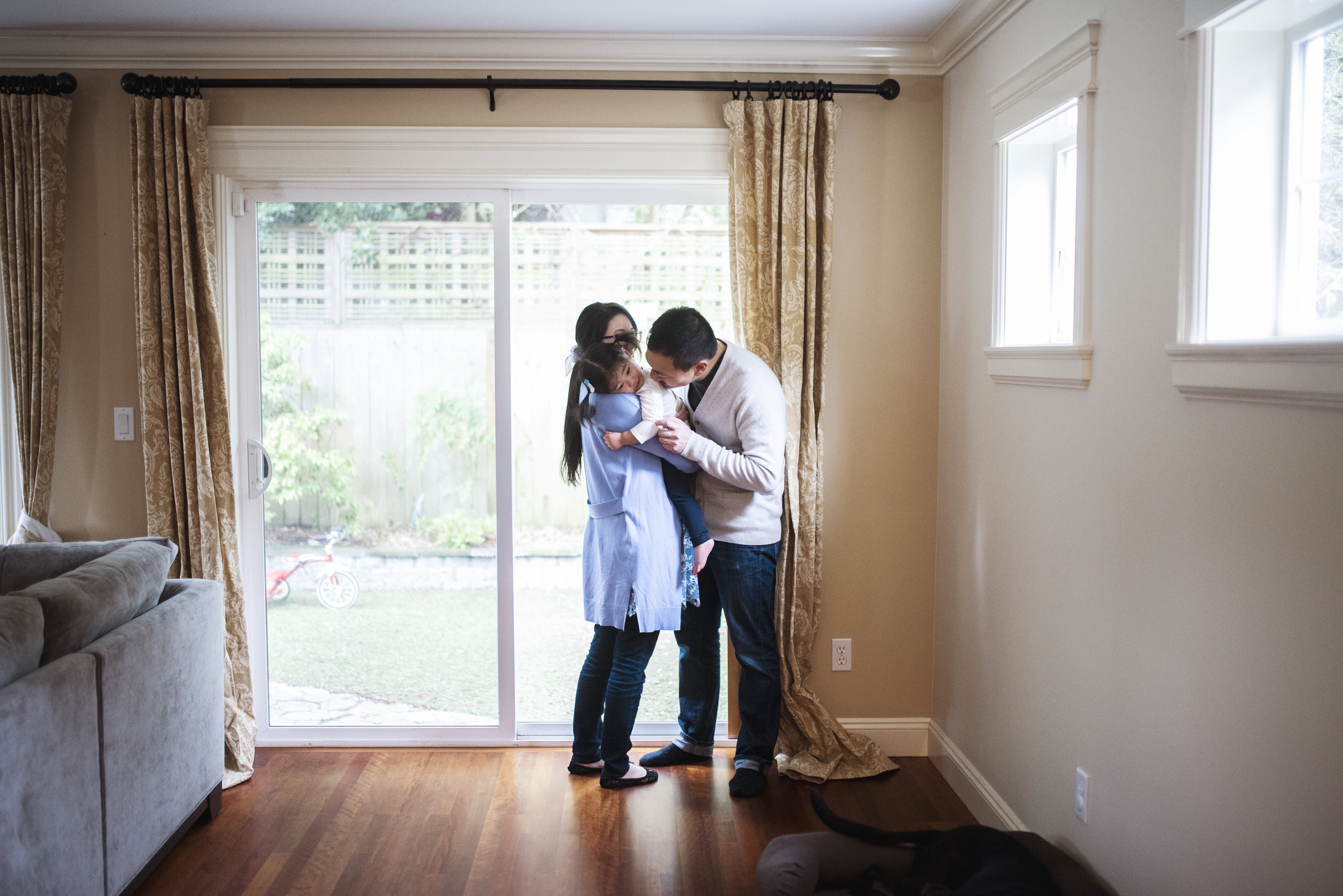 Seattle family photographer daughter is held by mom and dad while standing by glass door