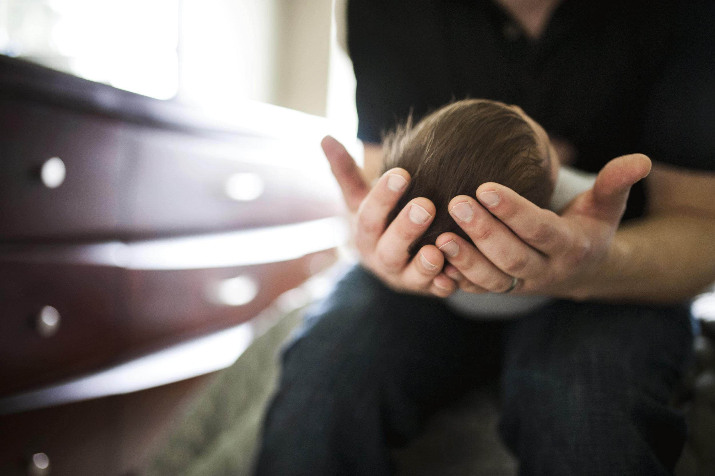 Everett Newborn Photographer dad holding baby's head in hands