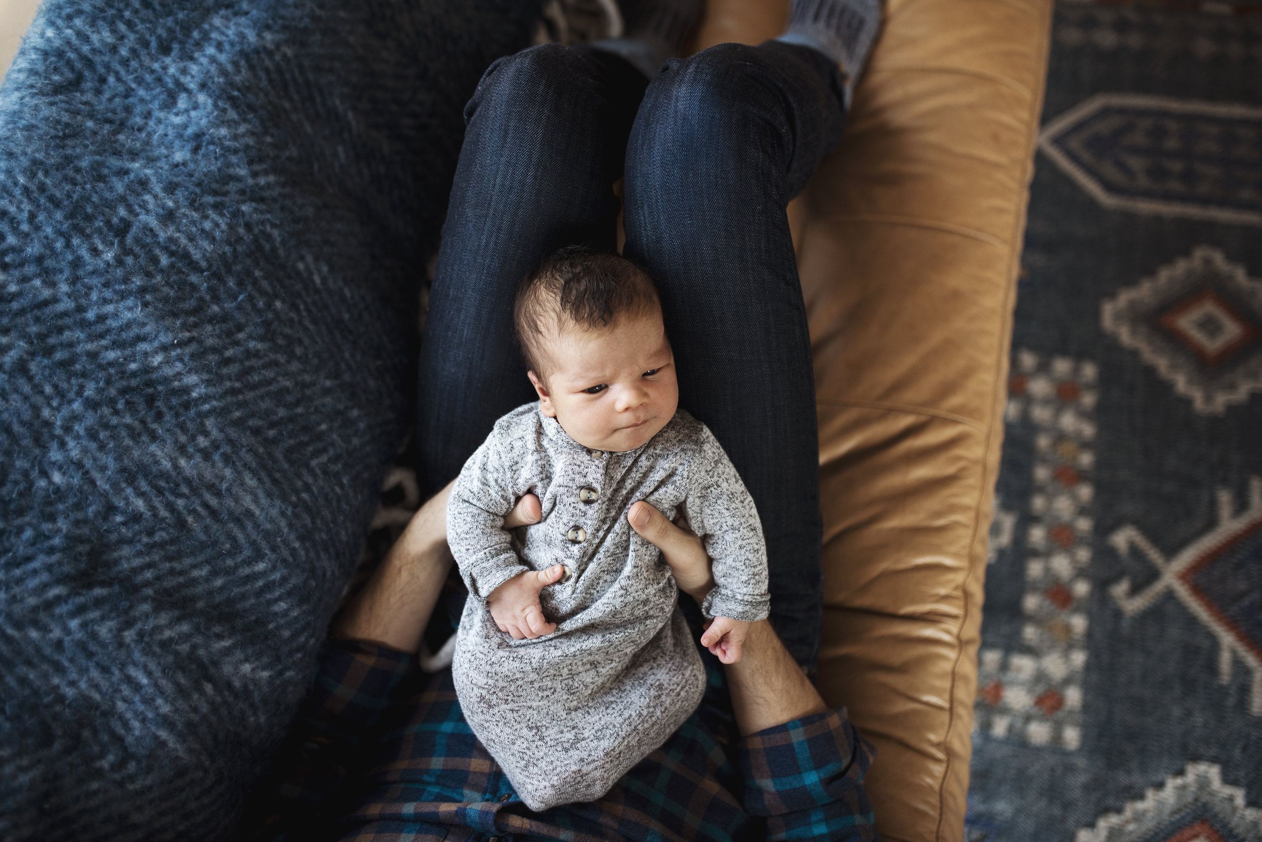 Newborn photographer Seattle baby is awake and on dad's lap on couch