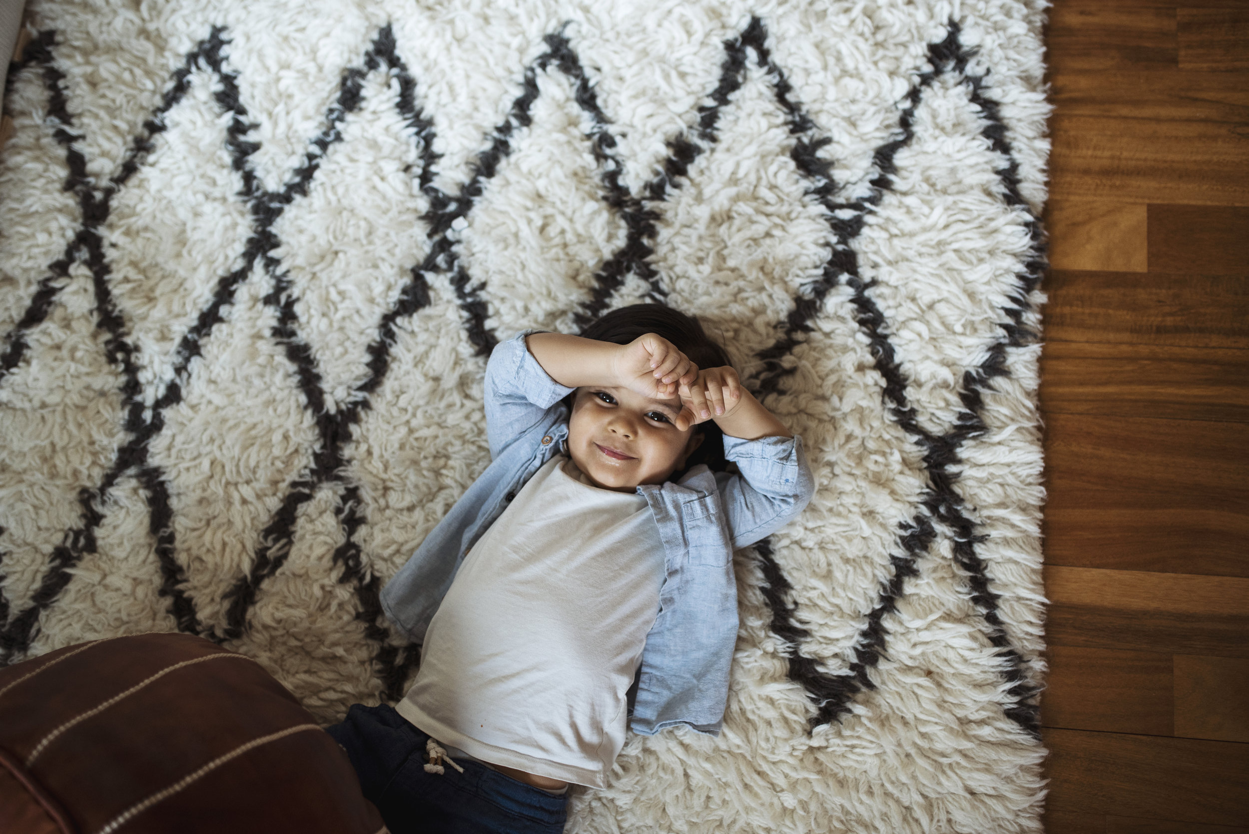 Newborn photographer Seattle boy is lying on rug smiling