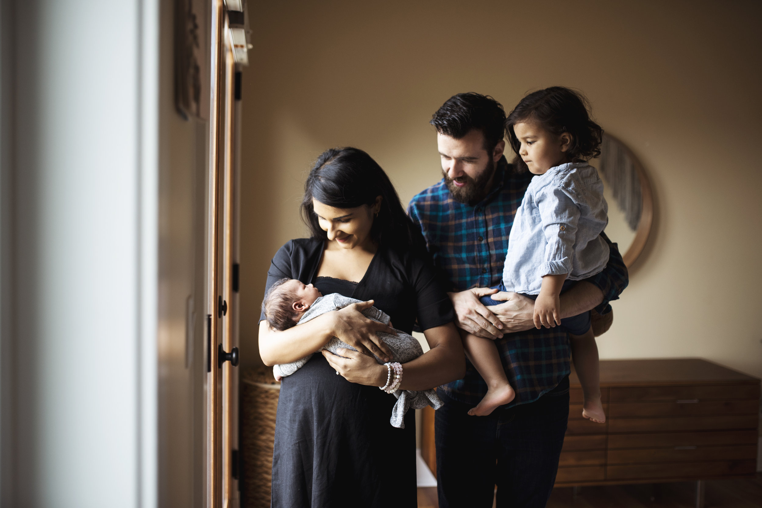Everett newborn photography family standing by window while mom holds baby, dad and big brother look on