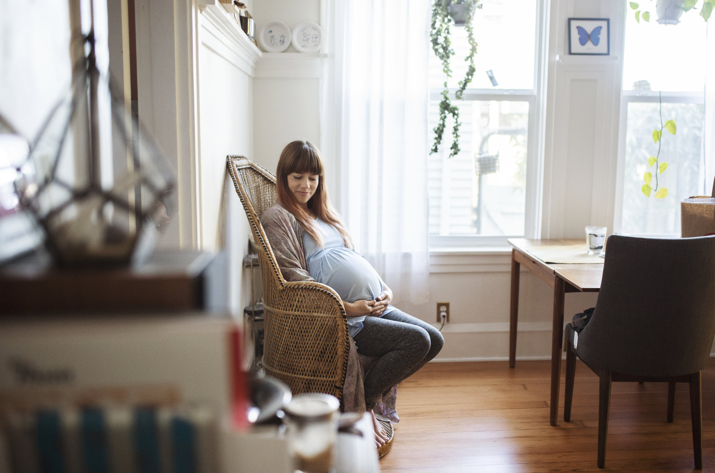 Seattle maternity photographer mom sits in a chair in the living room