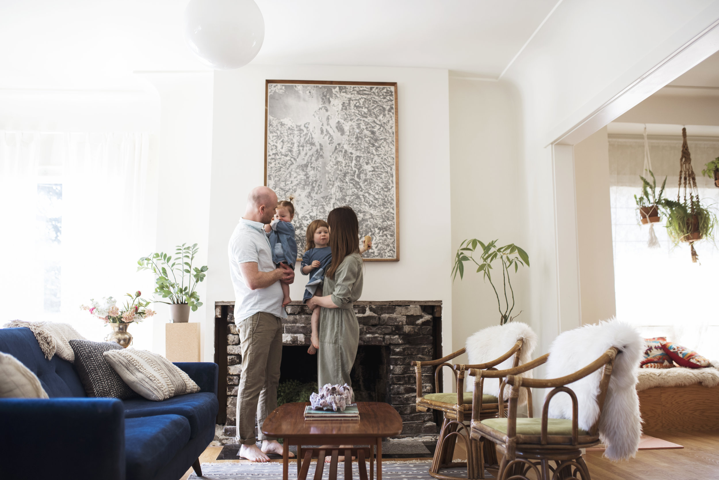 Seattle lifestyle photographer mom and dad hold two girls in front of fireplace in living room