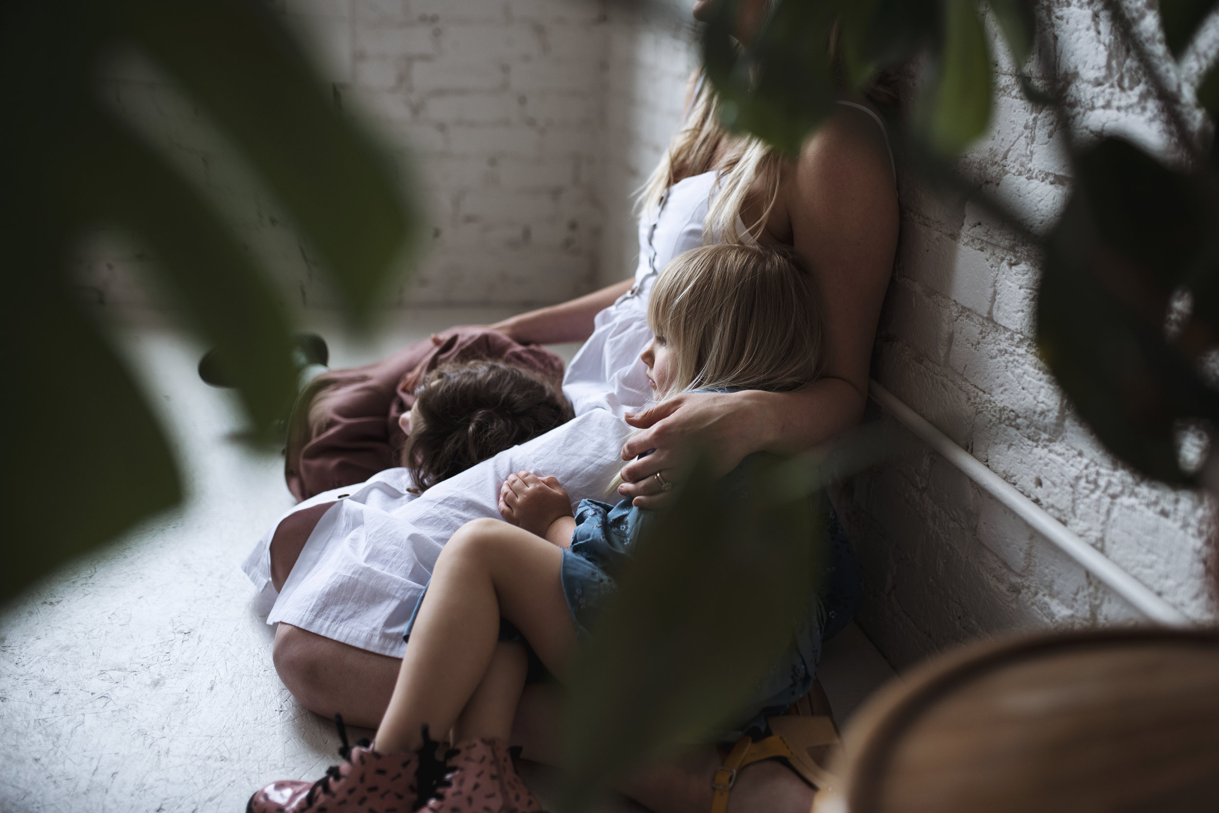 Seattle family photographer mom sits on ground with two daughters, surrounded by indoor plants