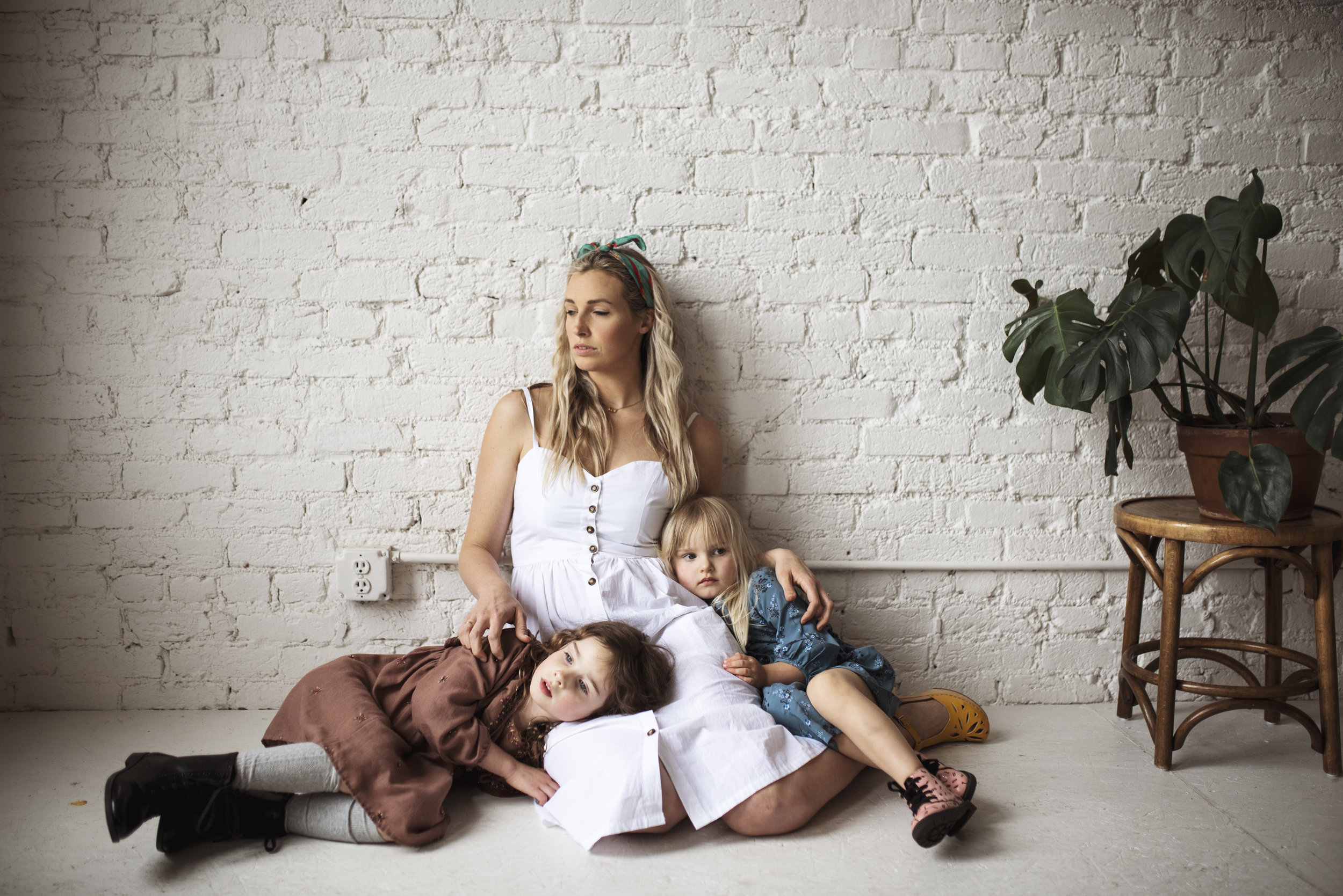 Seattle lifestyle photographer mom is sitting against white wall with daughters on her lap.