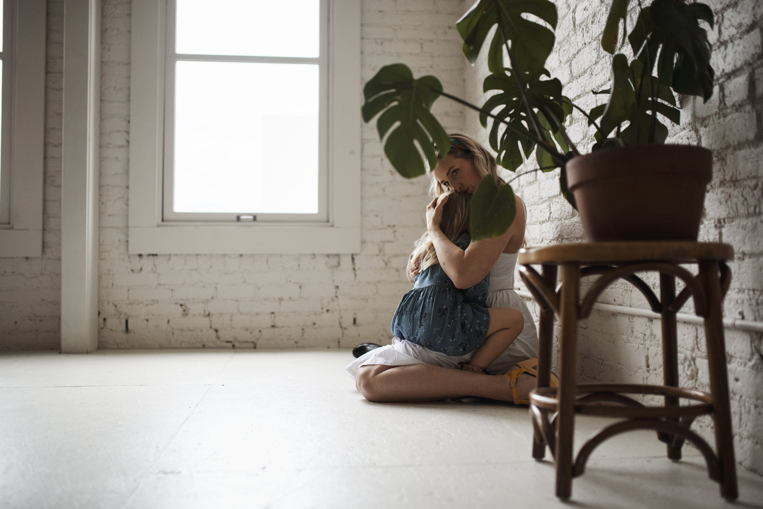 Seattle family photographers mom is holding daughter on floor with indoor plant next to them