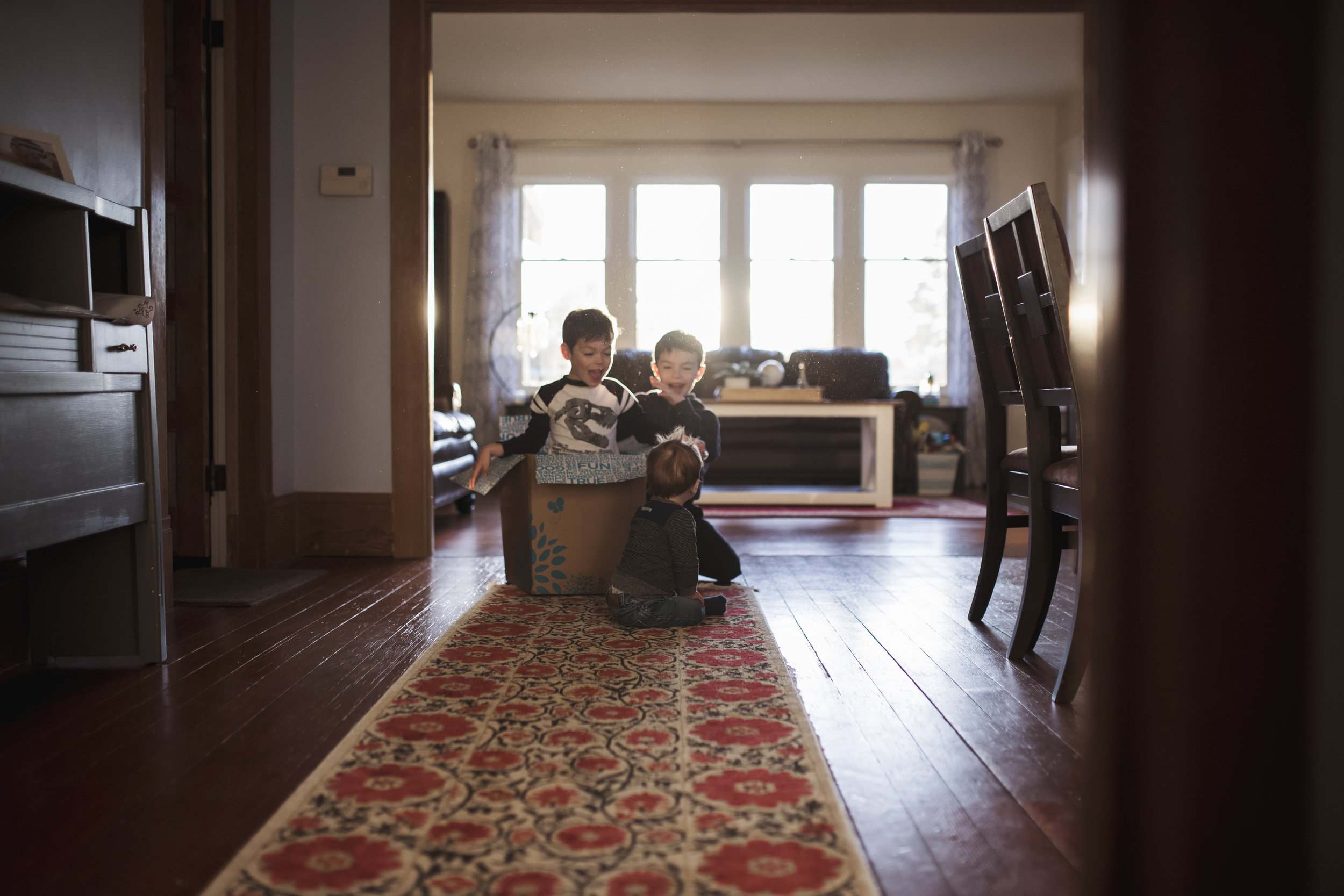 Seattle family photographer kids playing in box in living room