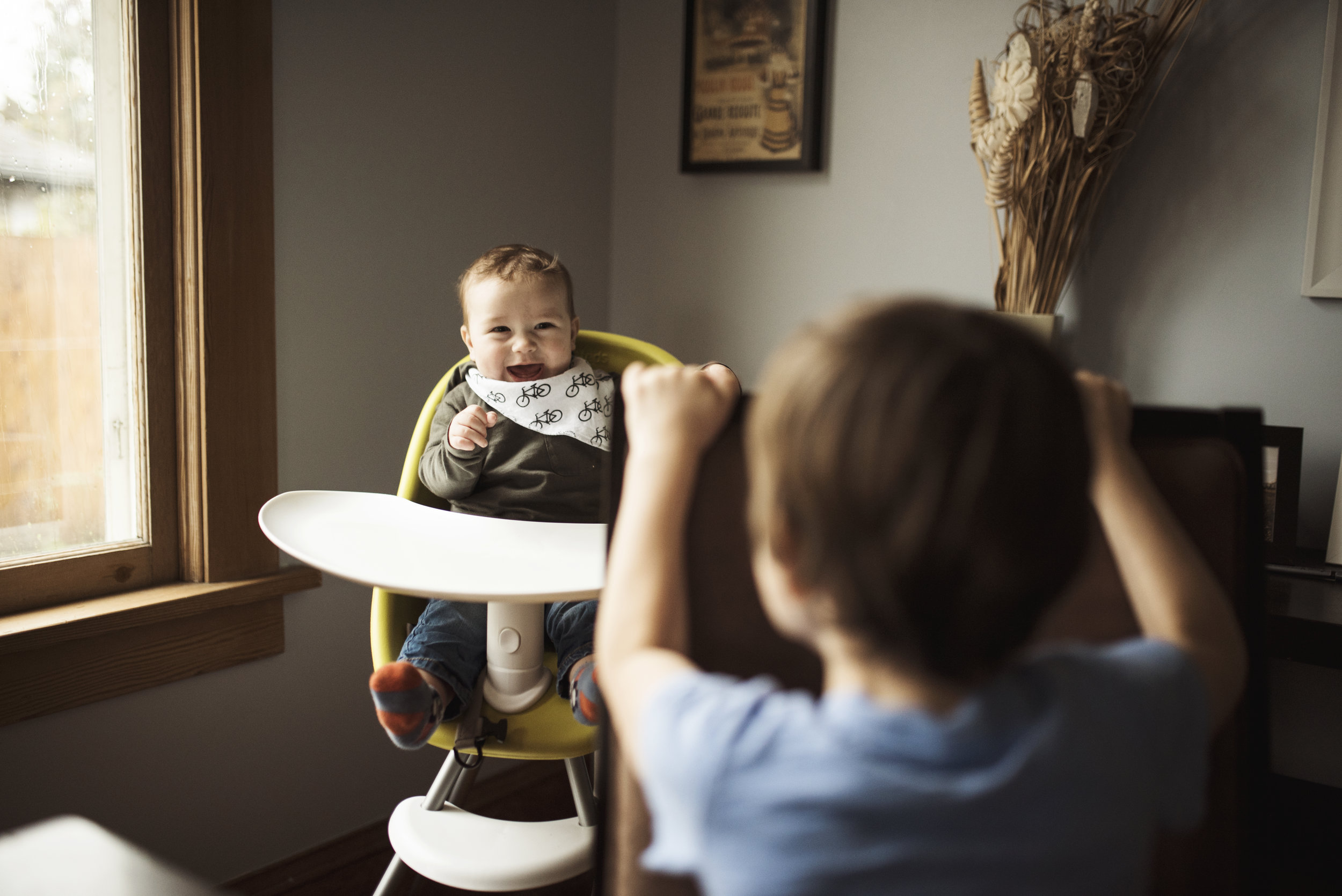 Seattle family photographer baby is sitting in highchair smiling at brother who is playing with him