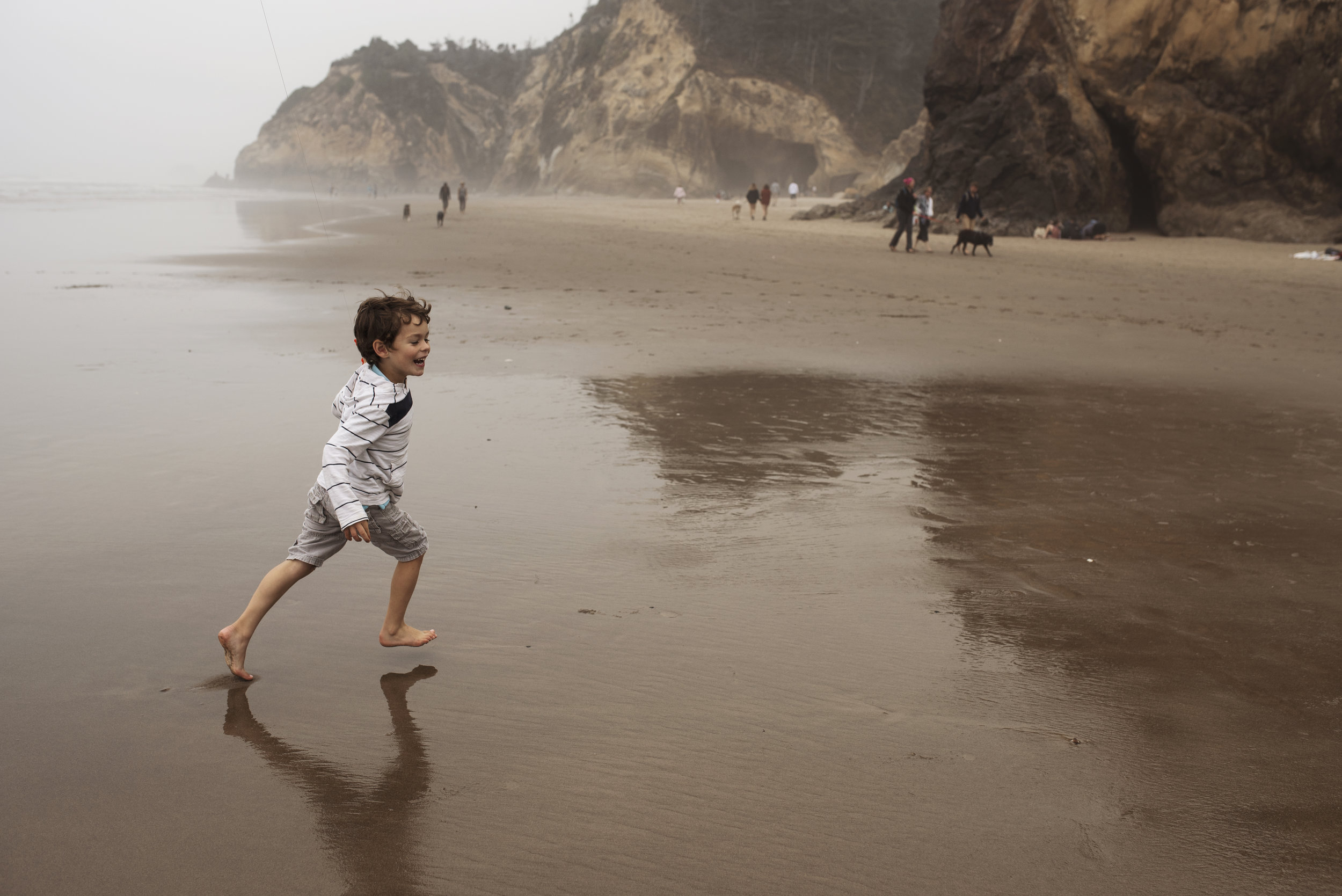 Seattle family photographer boy is running and smiling on a beach