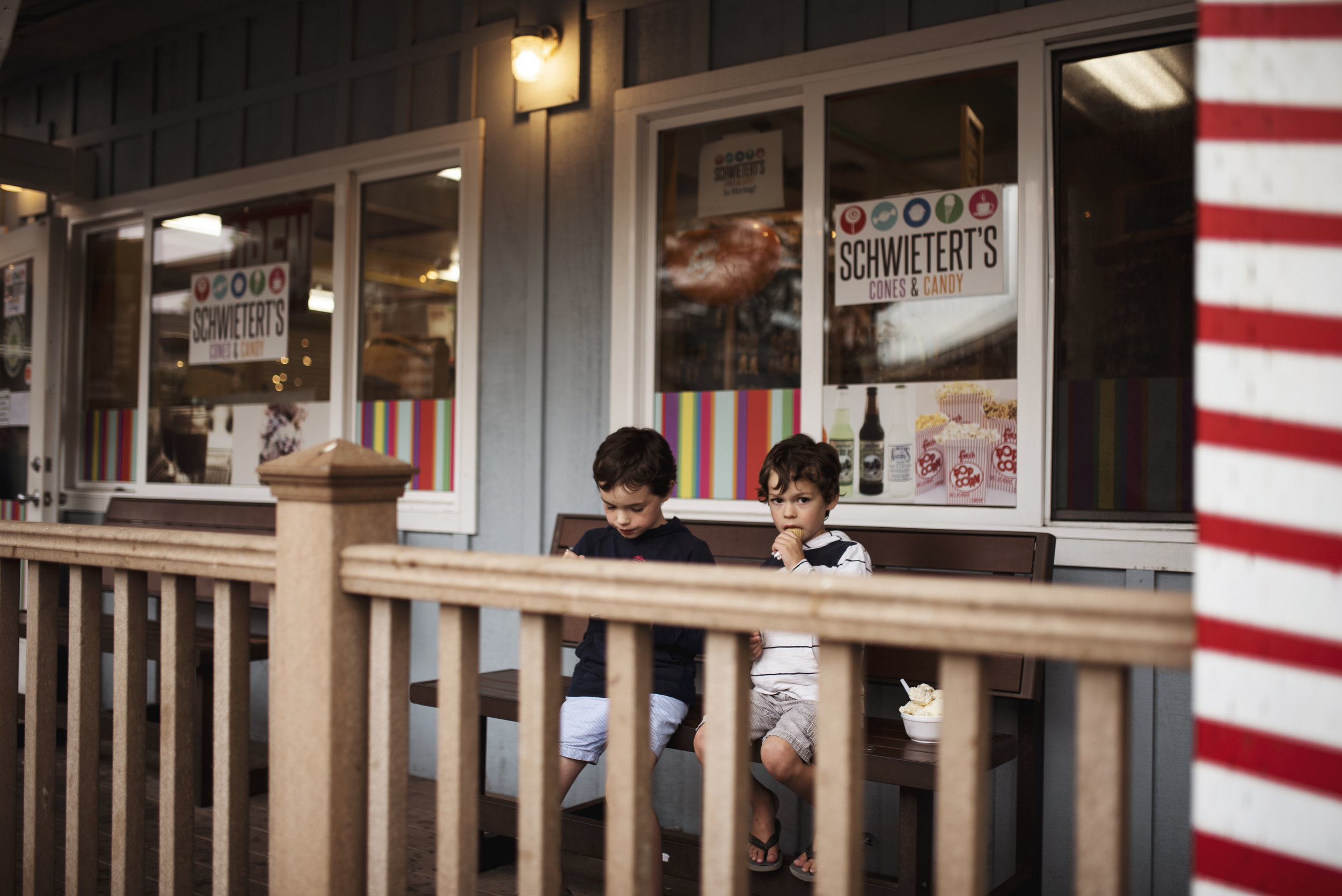 Seattle lifestyle photographer boys eating ice cream outside old fashioned candy store