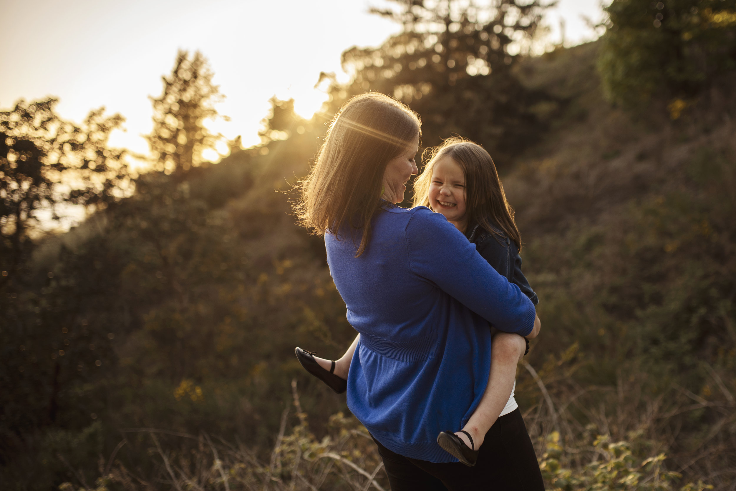 Seattle family photographer mom holding daughter at sunset