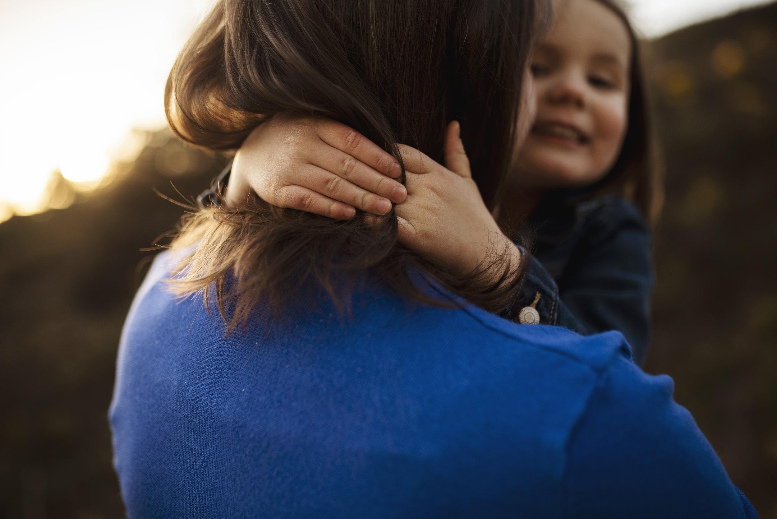 Everett family photographer close up of girls's hands around her mom's neck