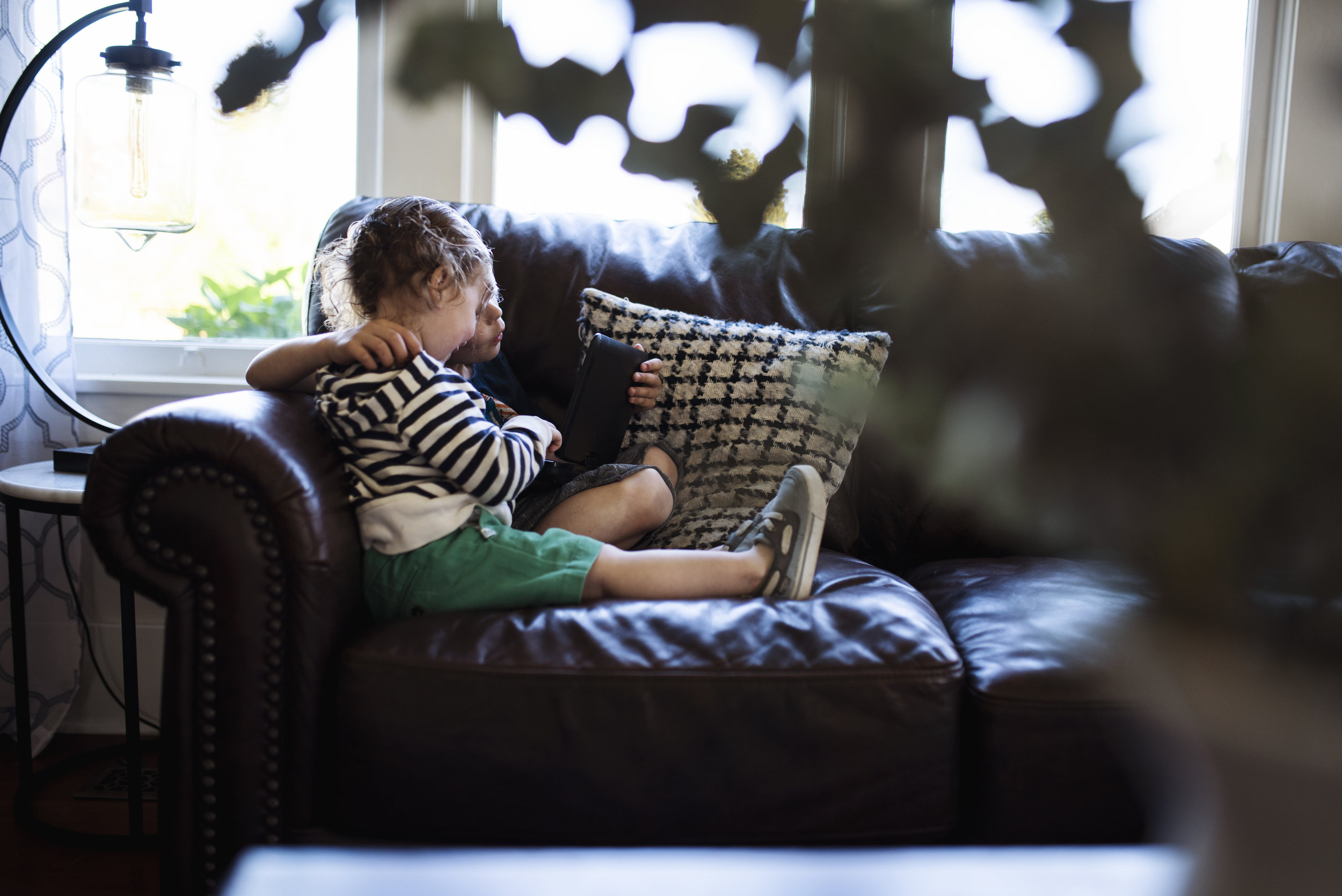 Lifestyle photographer Seattle two children are sitting on a couch looking at a book