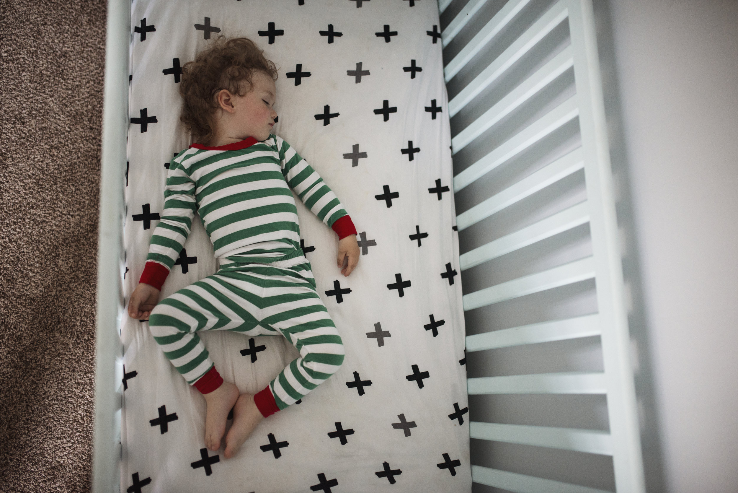 Seattle lifestyle photographer toddler asleep in his crib
