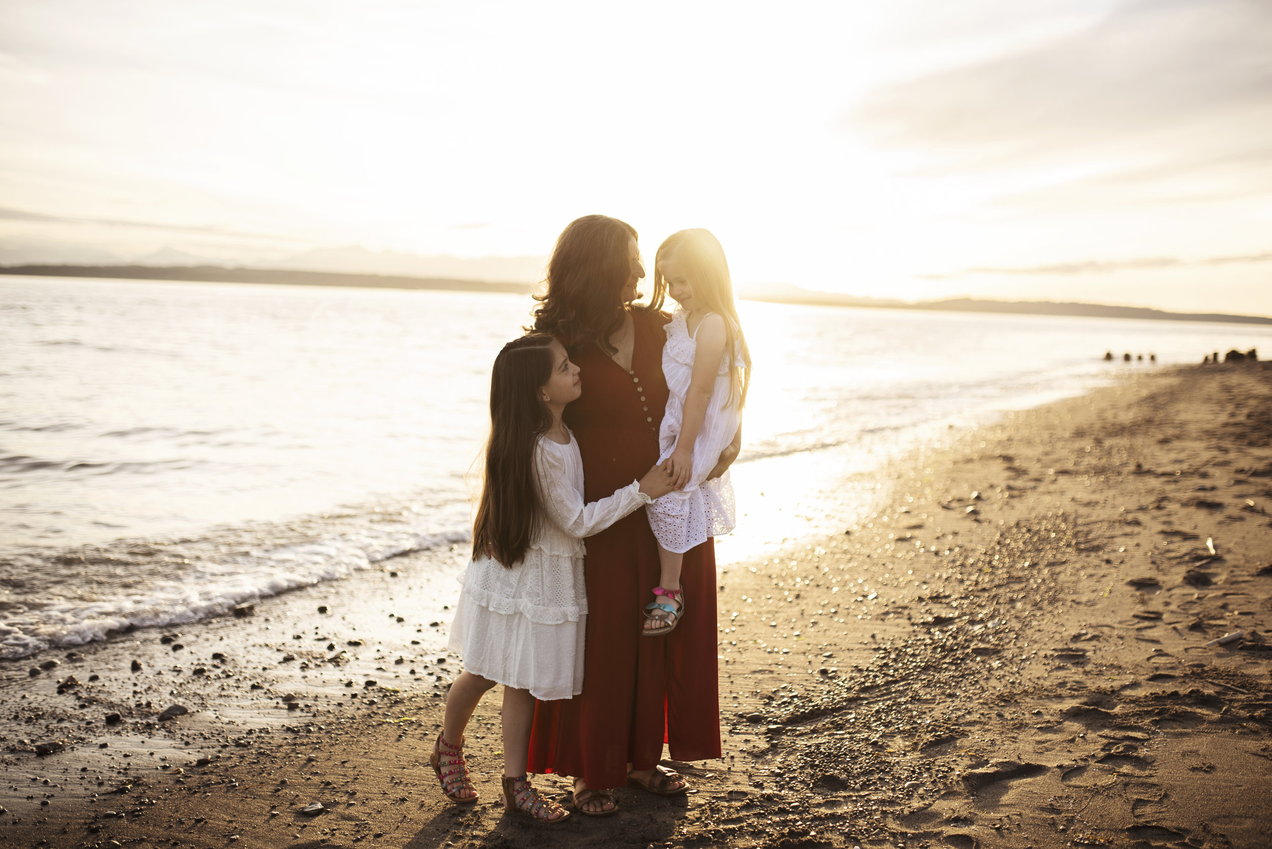 Lifestyle family photographer mom with two daughters on beach at sunset.