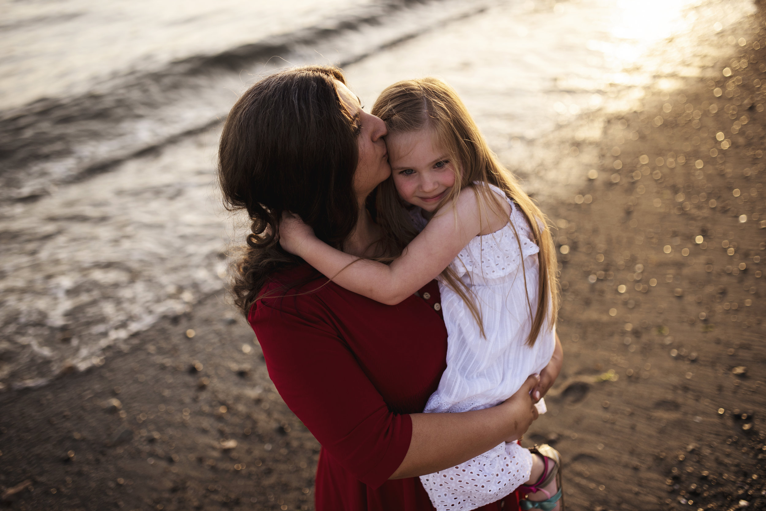 Lifestyle photographer Seattle mom holds little girl on beach at sunset
