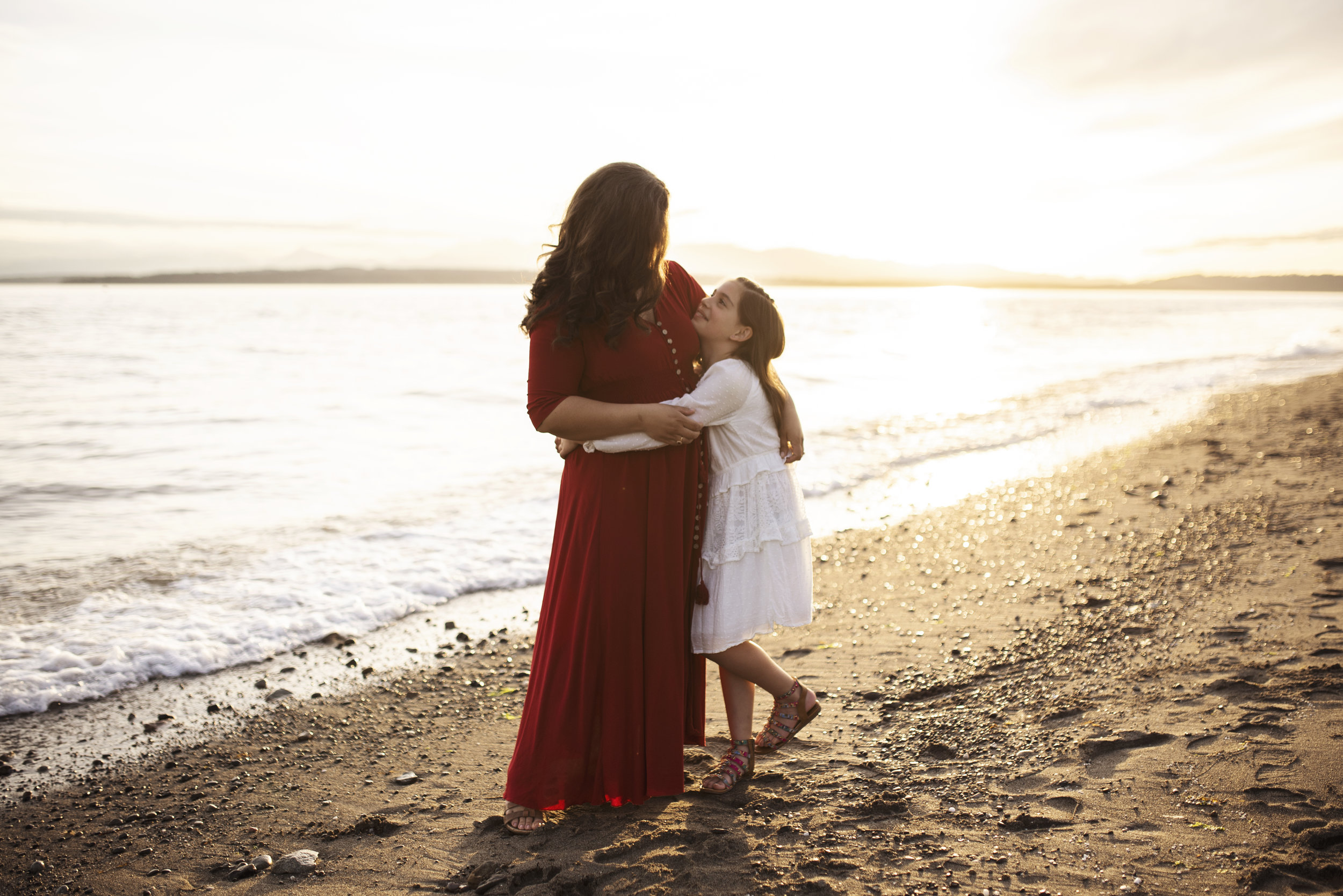 Seattle family photography  mom and daughter hug on beach at sunset