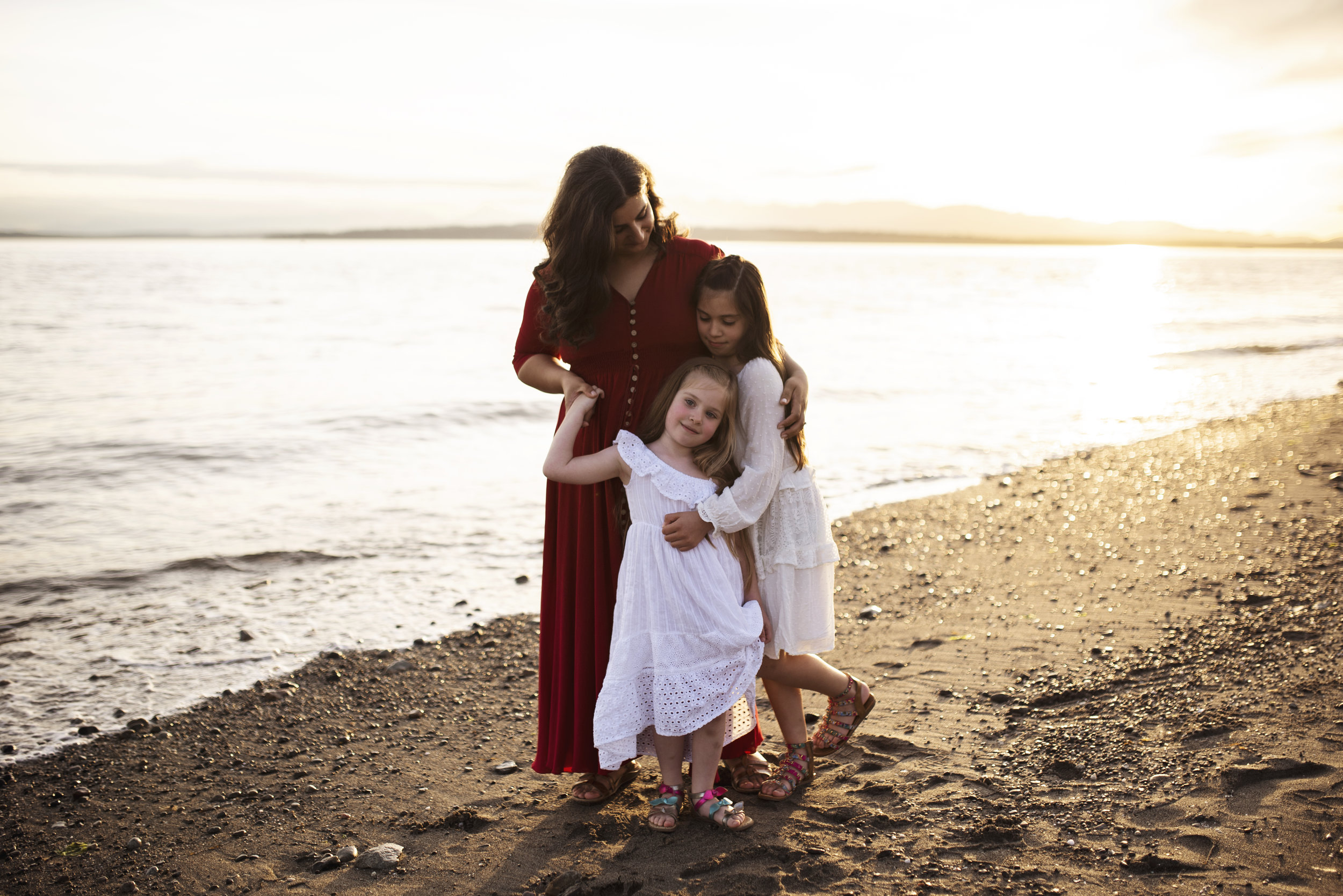 Seattle lifestyle photographer mom and girls hug on beach at sunset