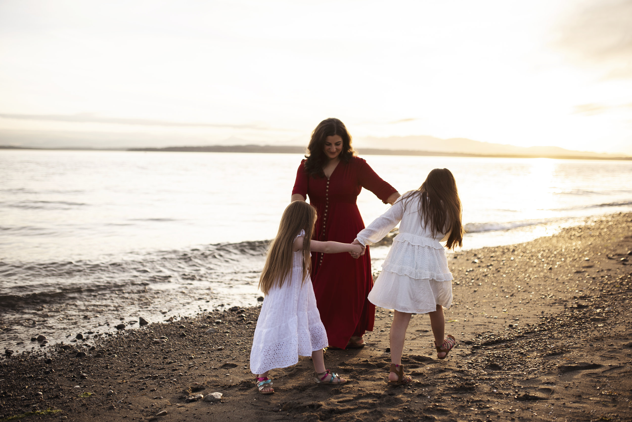 Lifestyle photographer Seattle mom is dancing with daughters on the beach at sunset