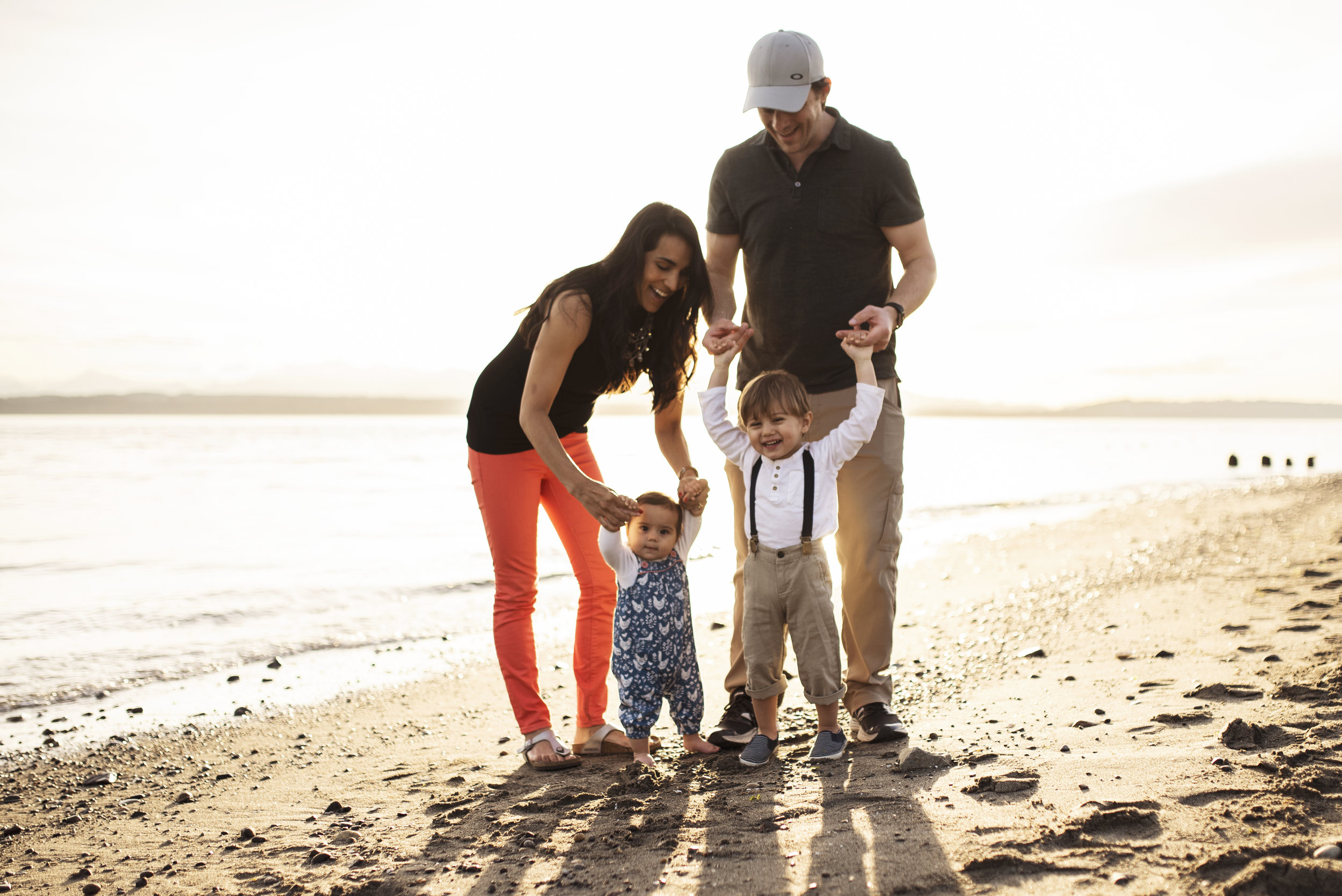 Lifestyle family photographer mom and dad with two children on beach at sunset