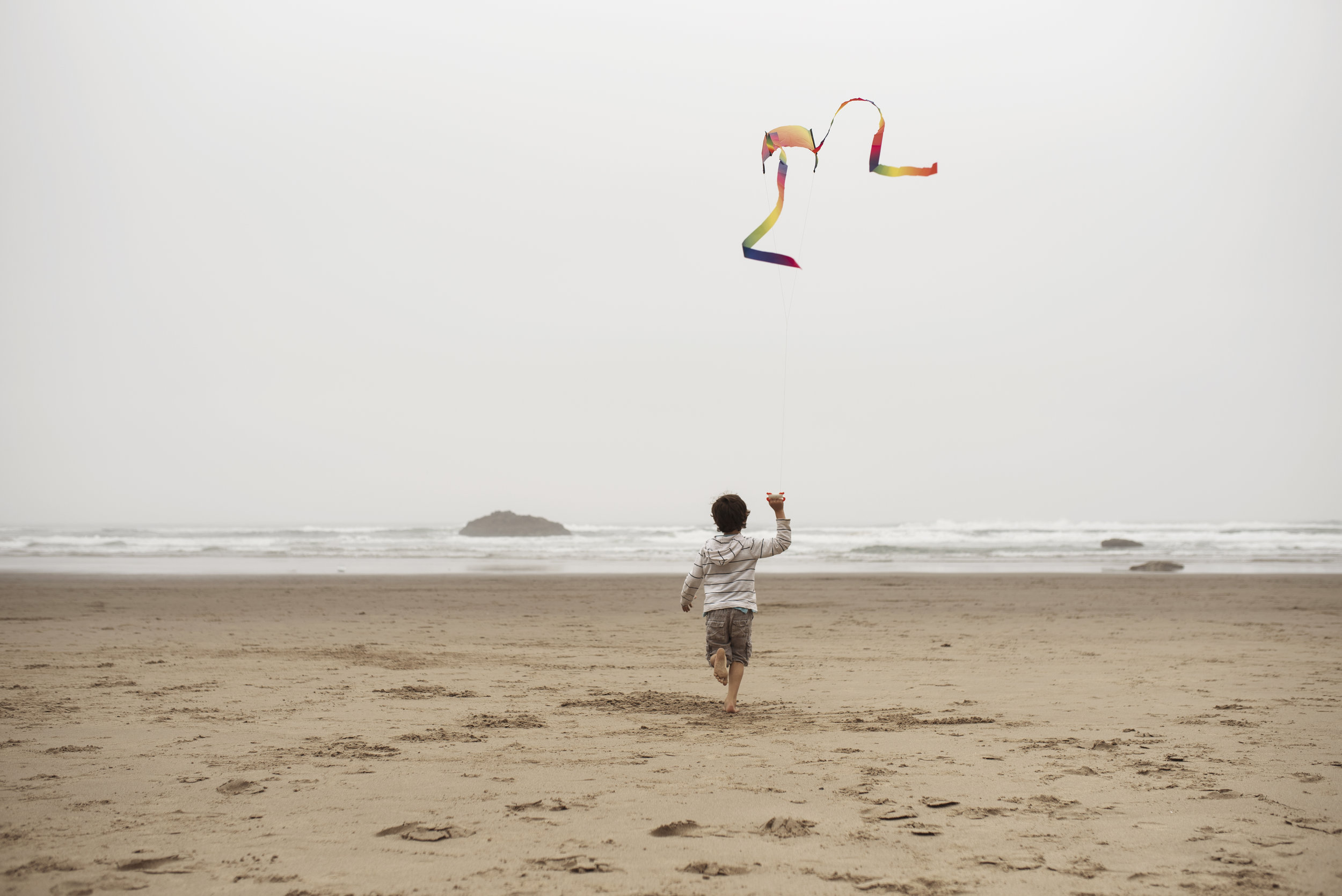 Seattle lifestyle photographer boy flying a kite on the beach