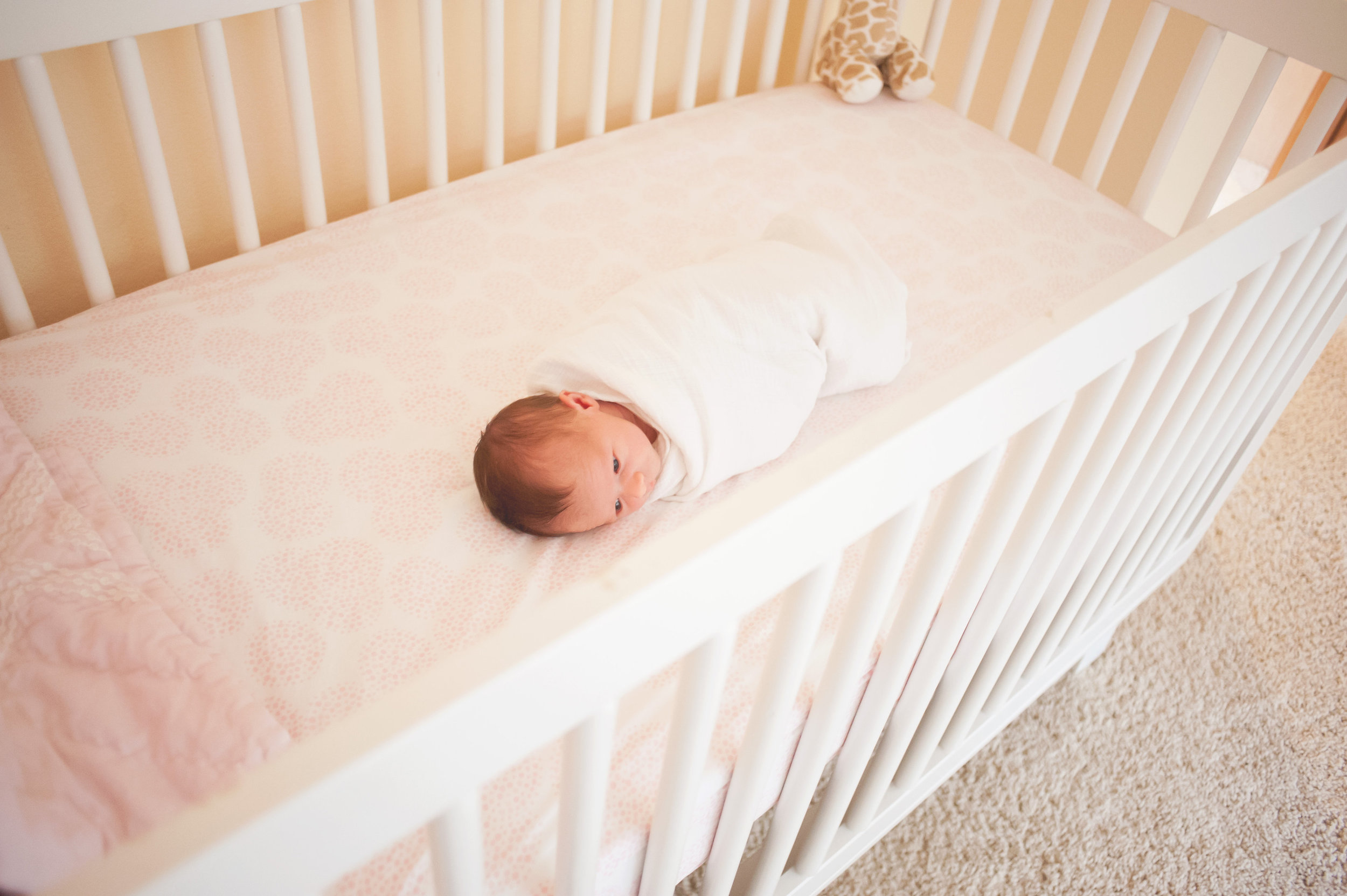 Seattle newborn photographer baby is lying in crib