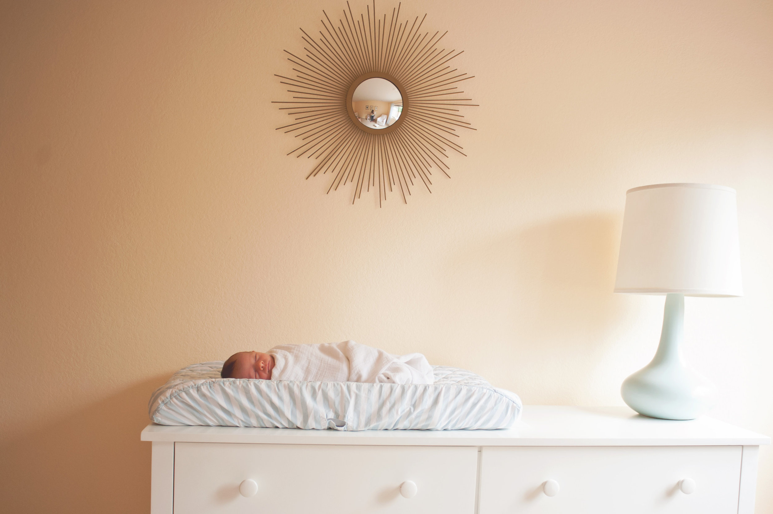 Lifestyle newborn photography baby is lying on changing table