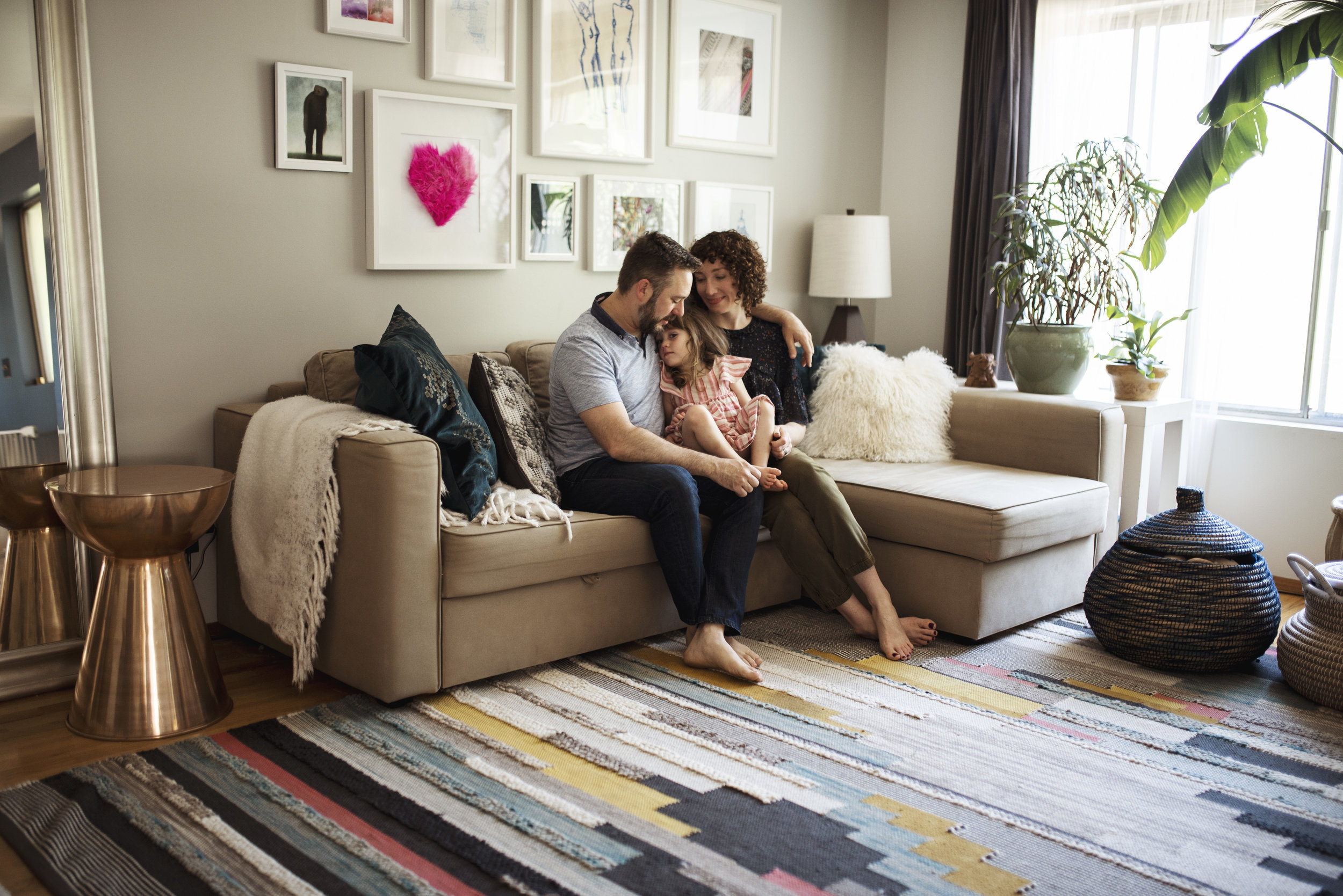 Lifestyle photographer Edmonds family is snuggling on couch in living room.