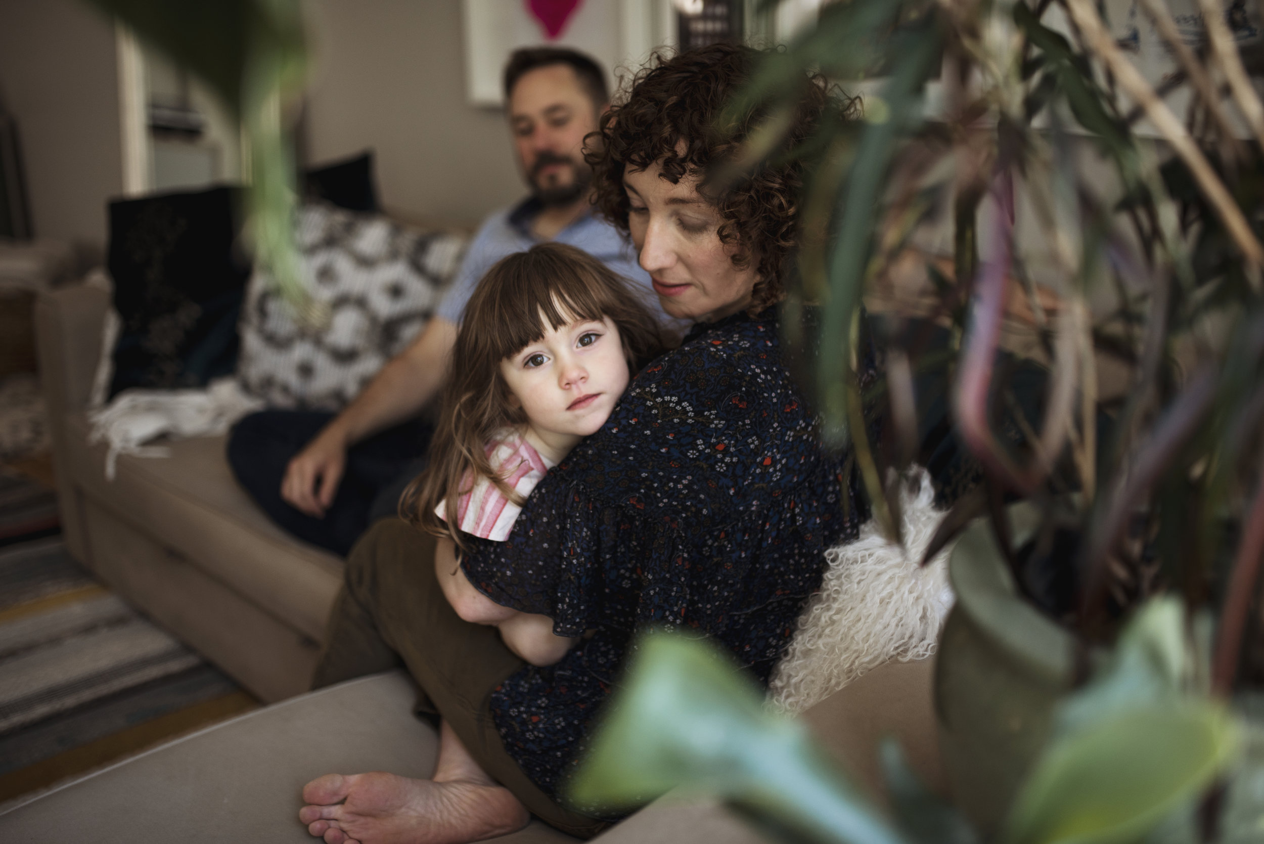 Everett family photographer parents on couch with daughter