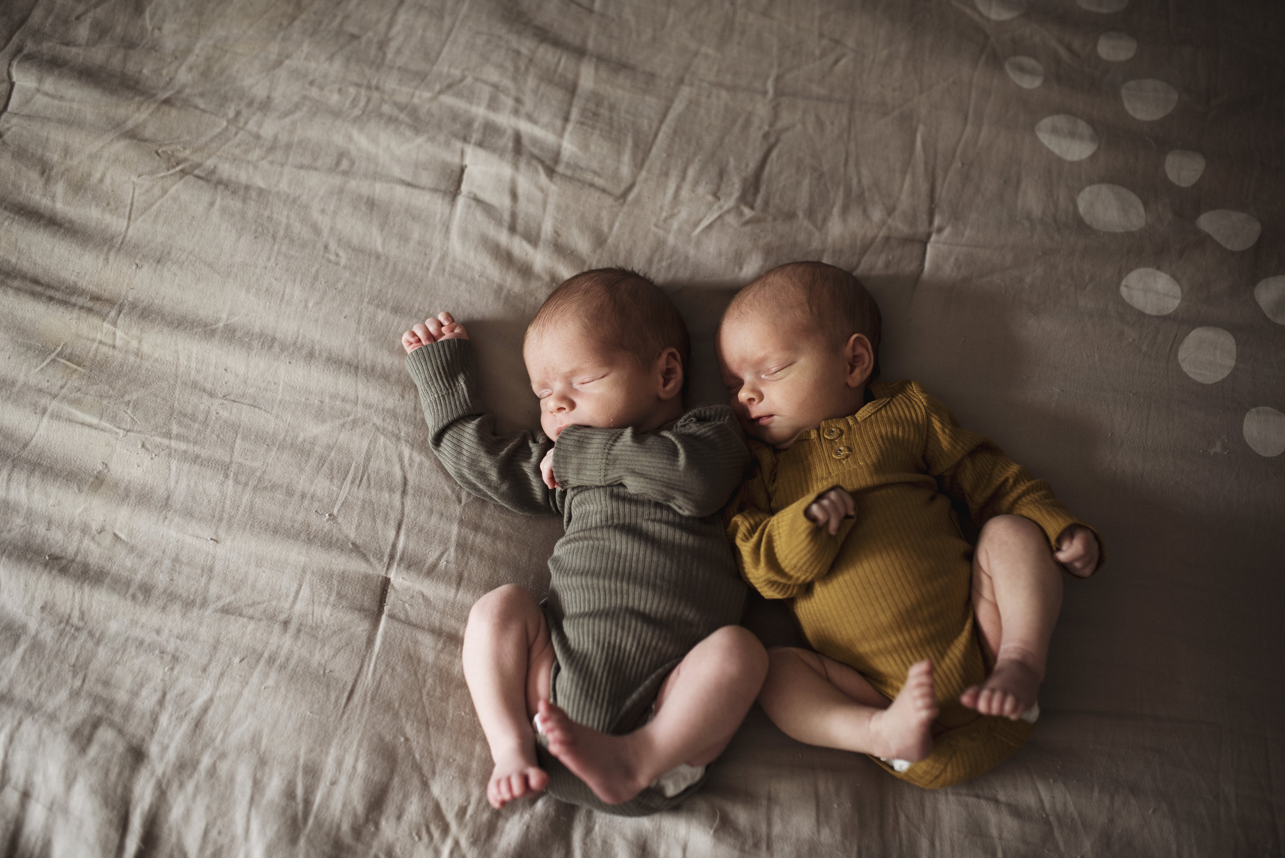 Edmonds newborn photographer twin babies are sleeping on a bed
