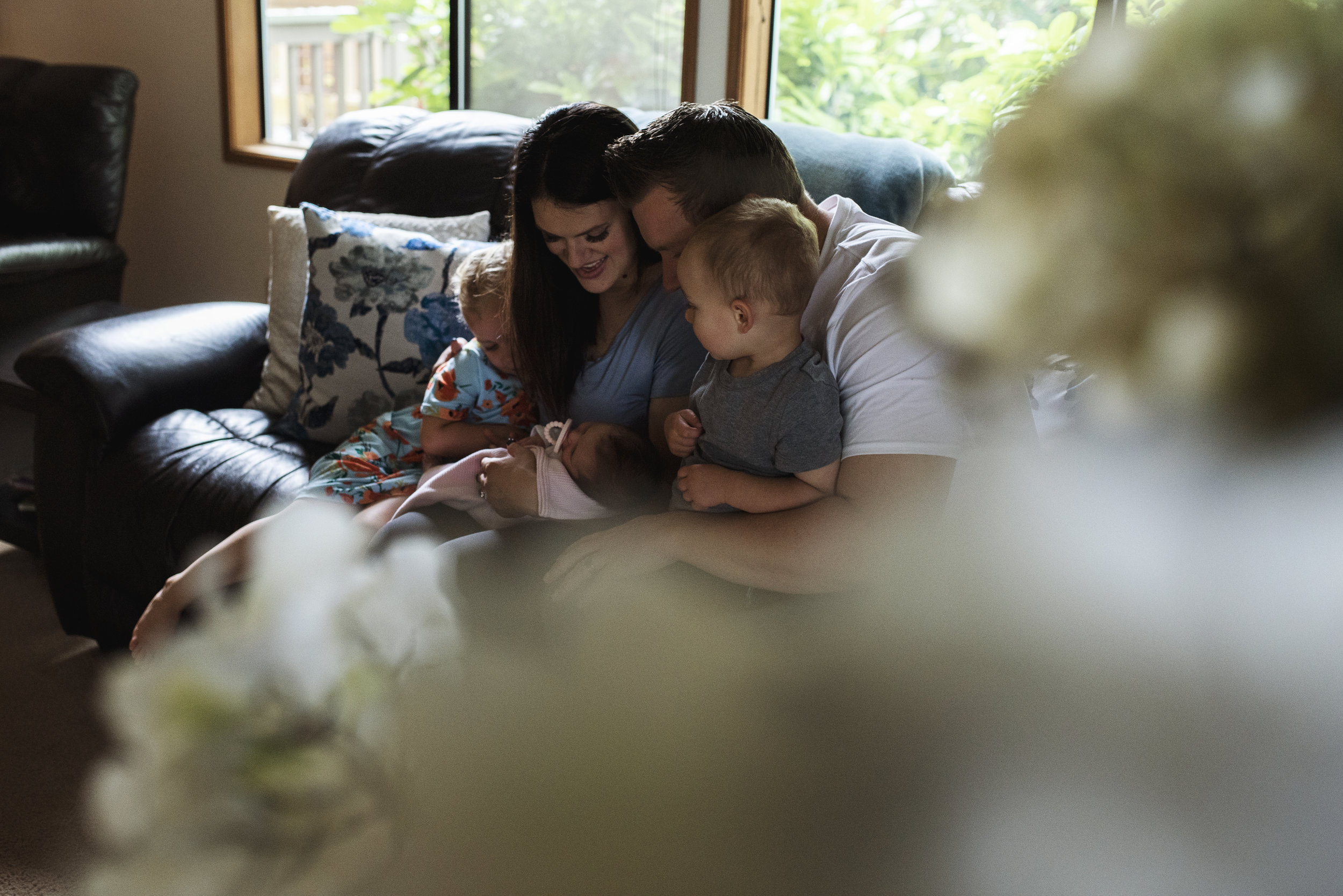Seattle lifestyle photographer family of five sit on the couch looking at their newborn