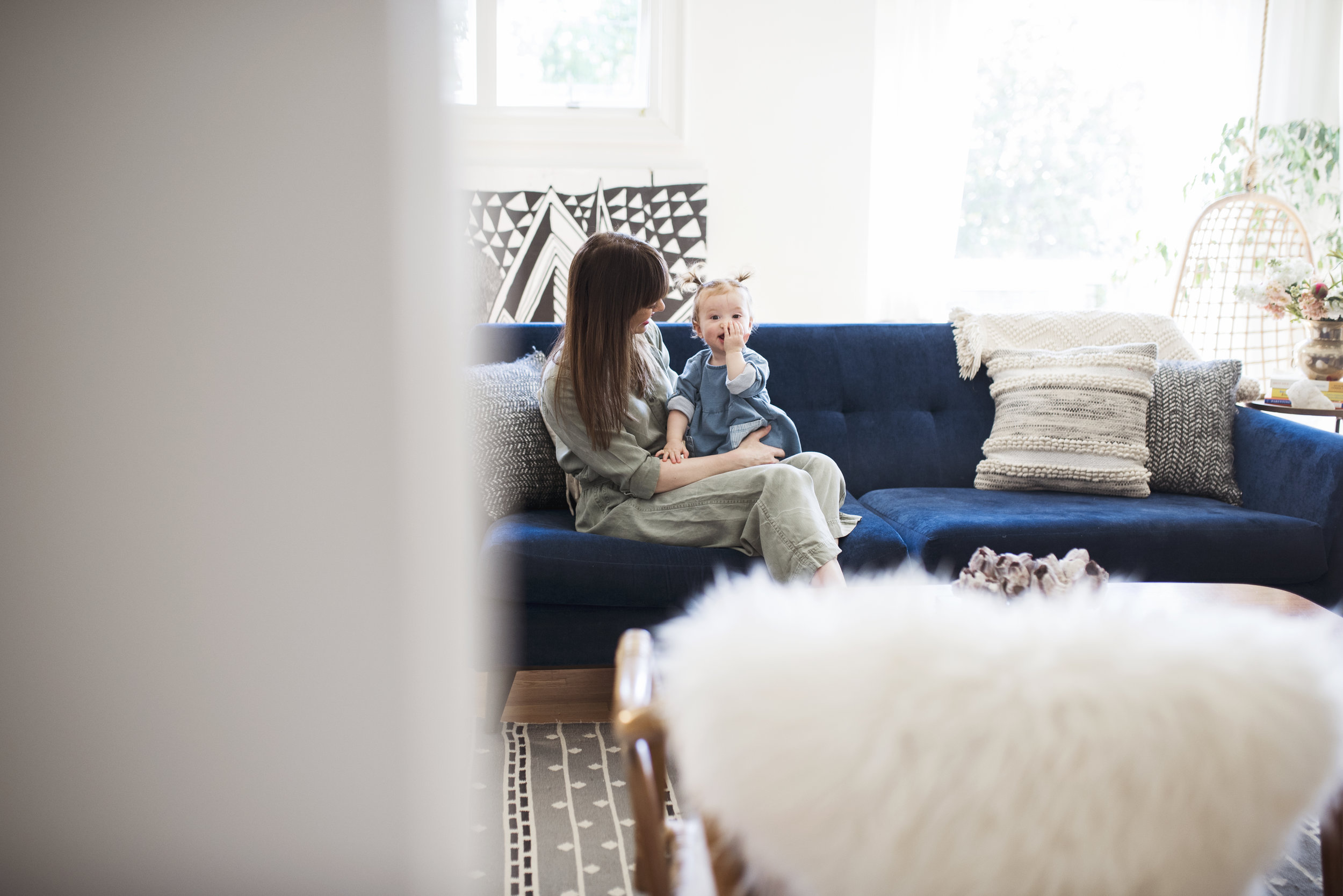 Seattle family photographer mom is holding baby girl on the couch