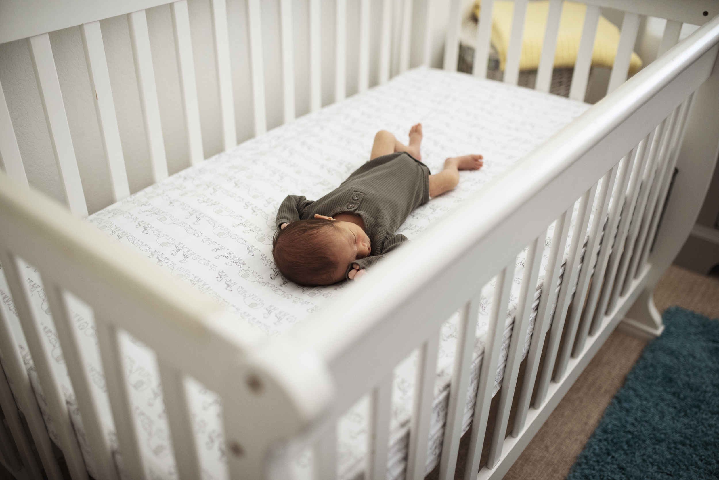 Seattle lifestyle photographer newborn baby is asleep in the crib