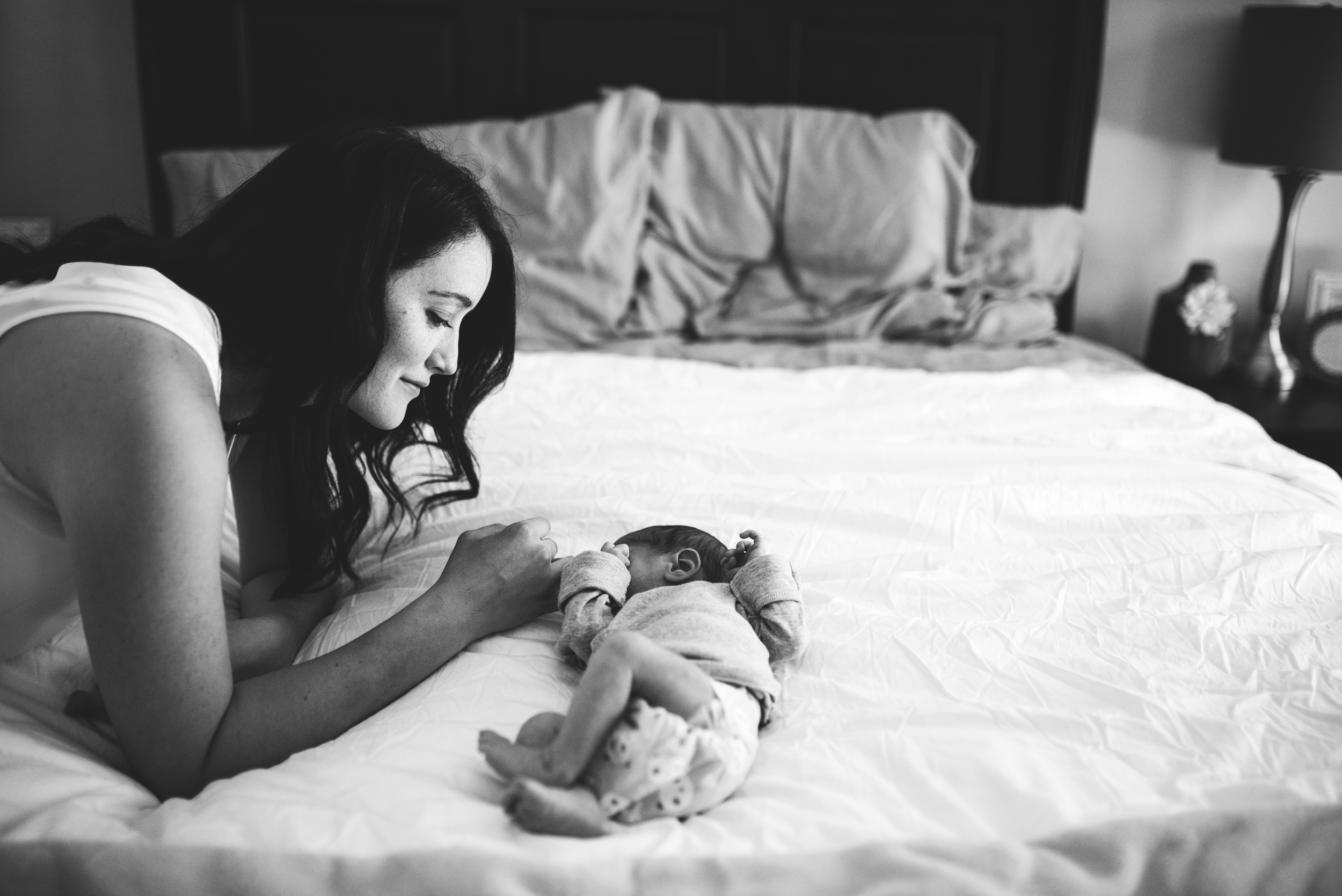Everett newborn photographer baby is on bed while mom looks on