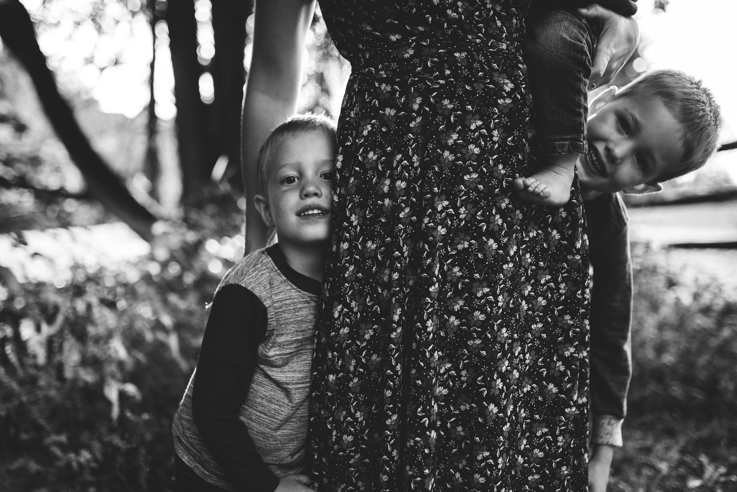 Seattle lifestyle family photographer boys are peeking out from behind mom