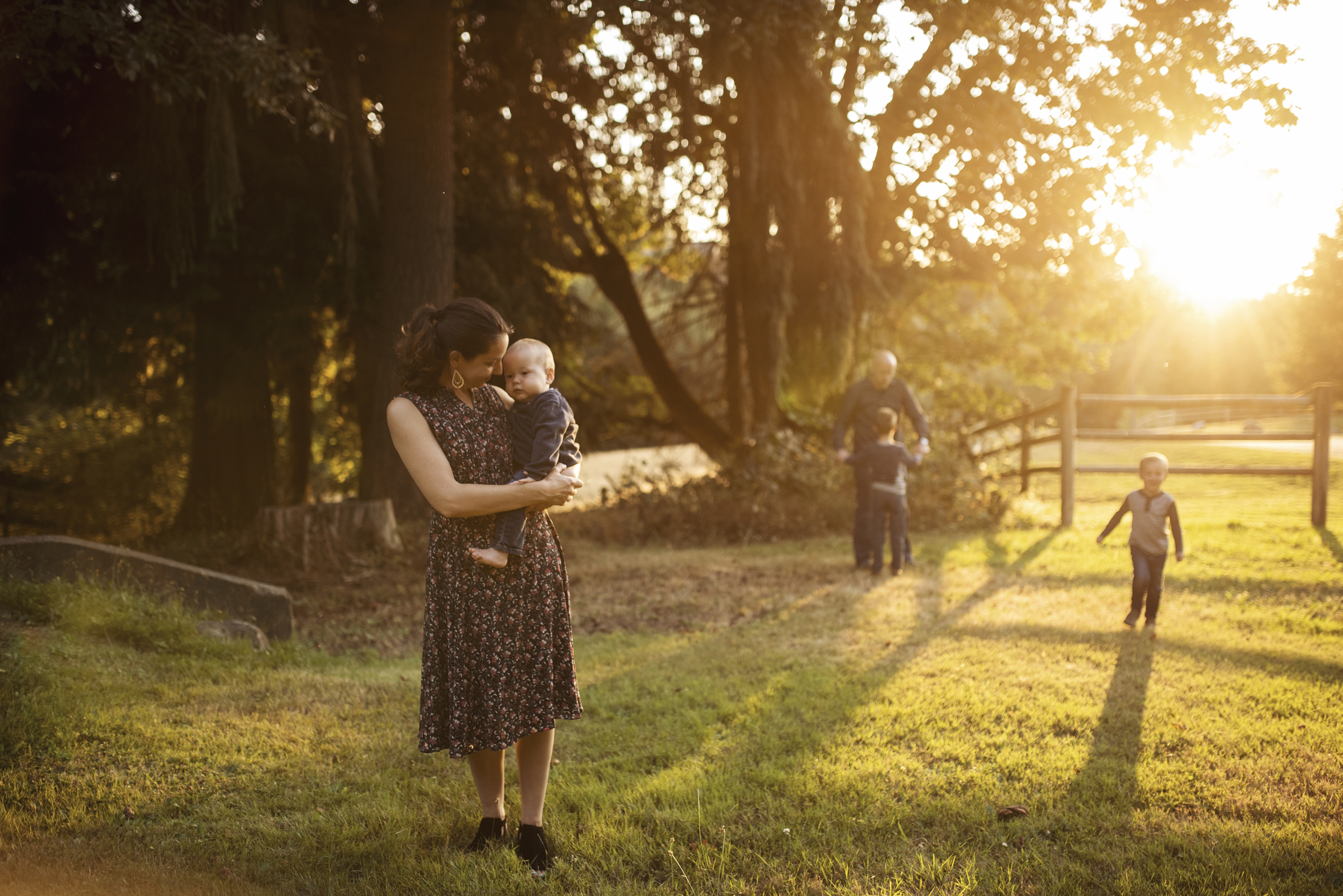 Seattle lifestyle photographer mom is holding baby while big kids and dad play in background