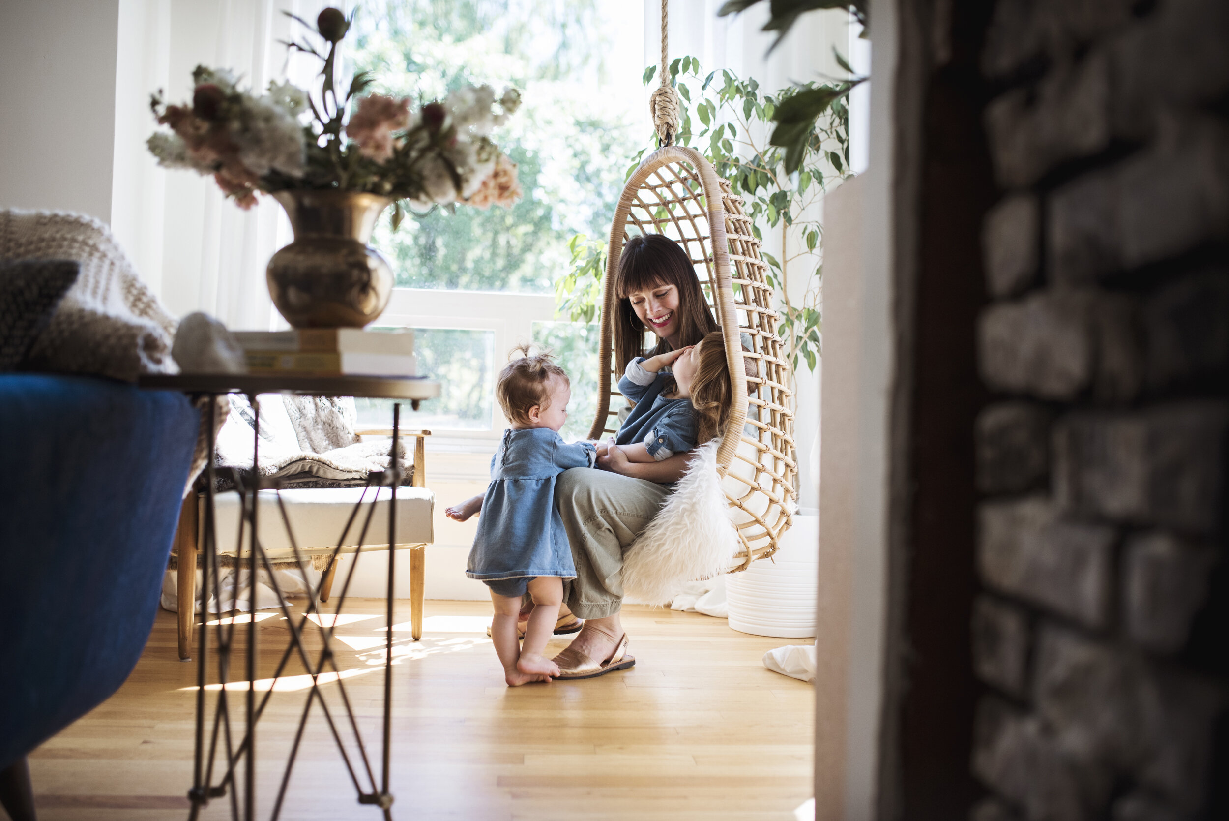 Edmonds family photographer mom is sitting on swinging chair with daughters
