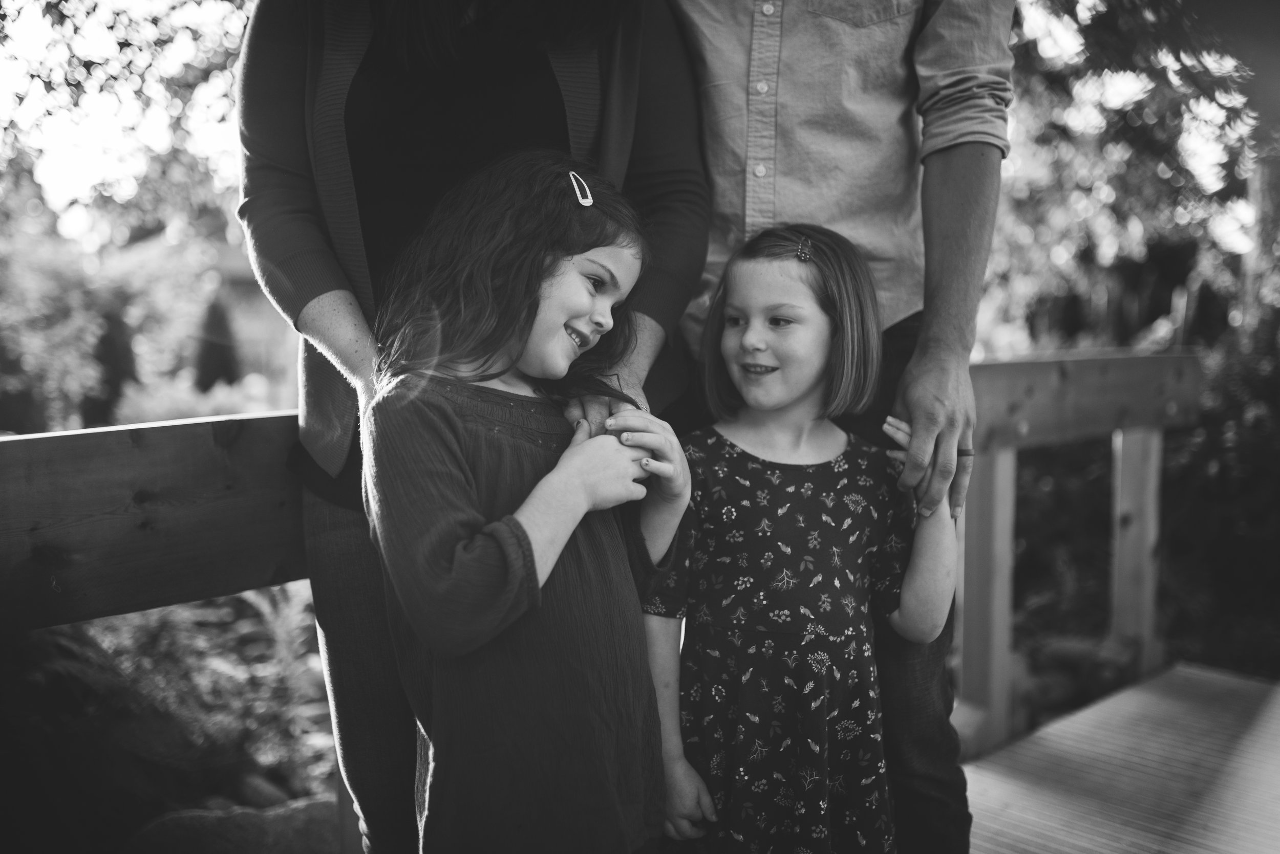 Everett family photographer girls standing together cuddled by parents
