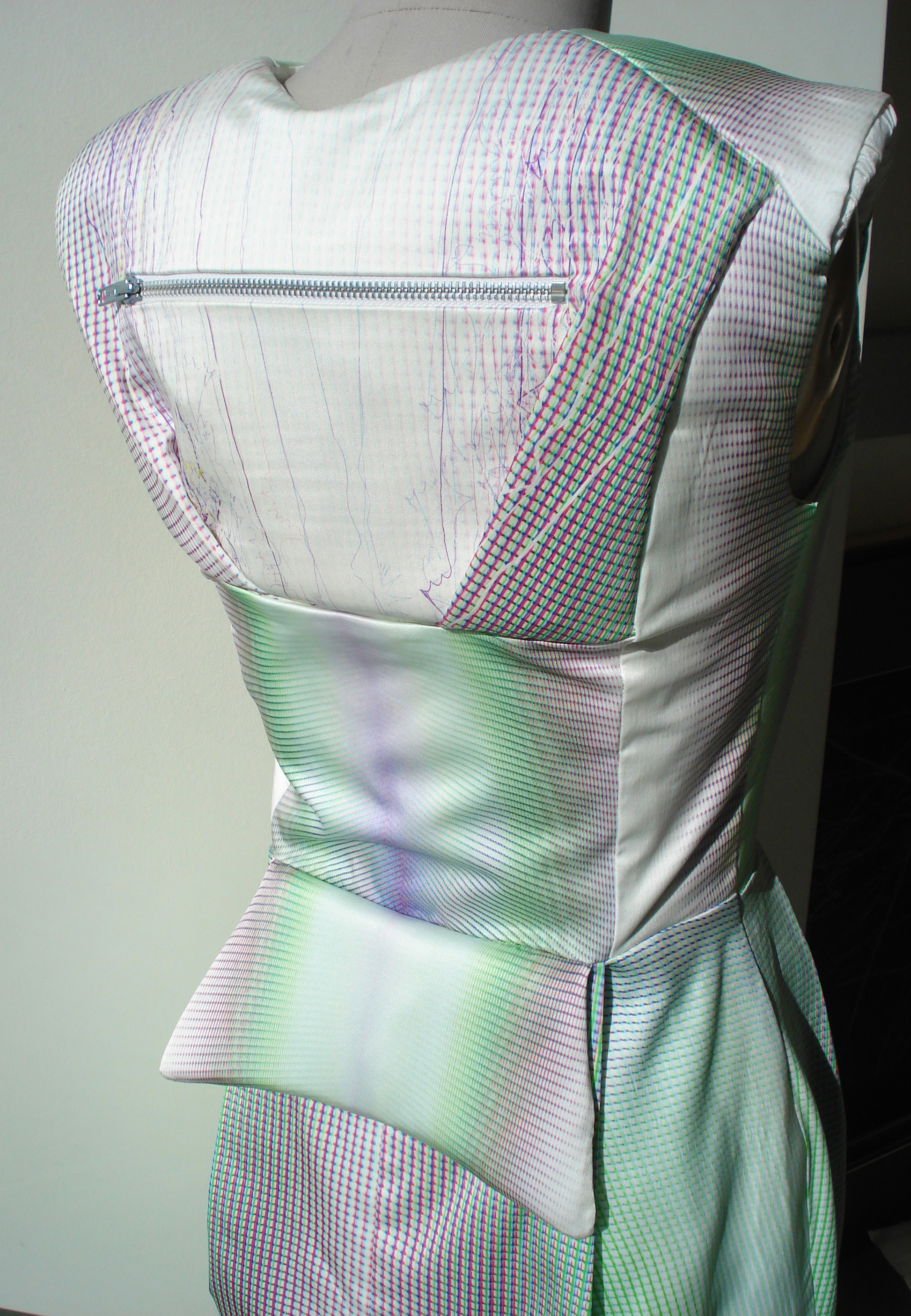 Back dress: Upper back holds electronics in backpack-like pocket. Lower back lumbar cushion is in the down position. When up, the energy builds. When down, the energy is released and a burst of light forms at front of the dress.